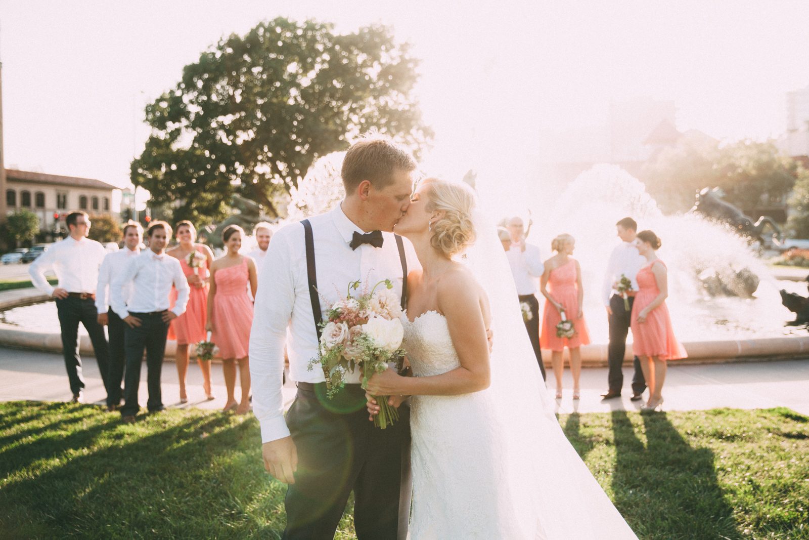 Bride and groom kissing with wedding party in front of famous JC Nichols Kansas City fountain