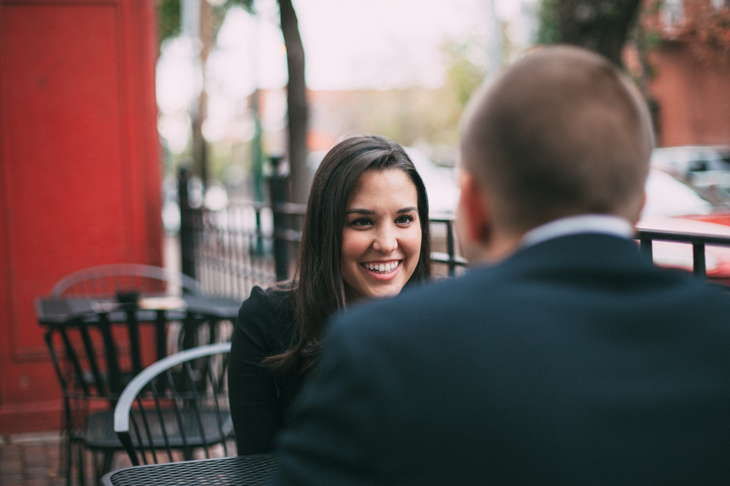 Engaged couple sitting at a patio table