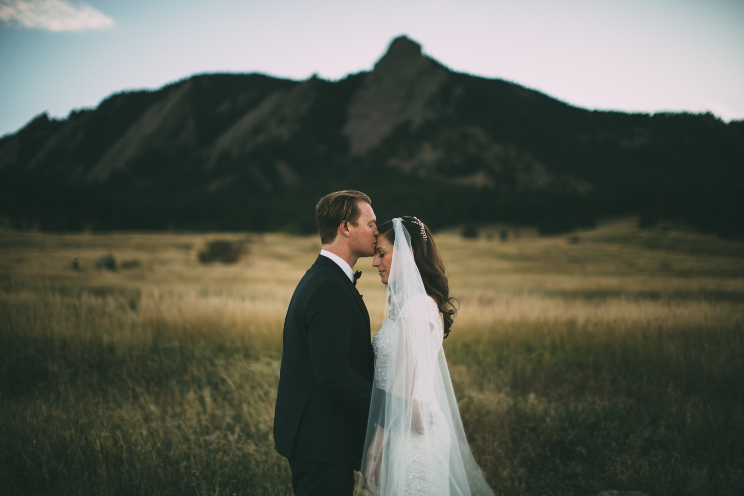 bride and groom in a meadow in front of a mountain in boulder colorado
