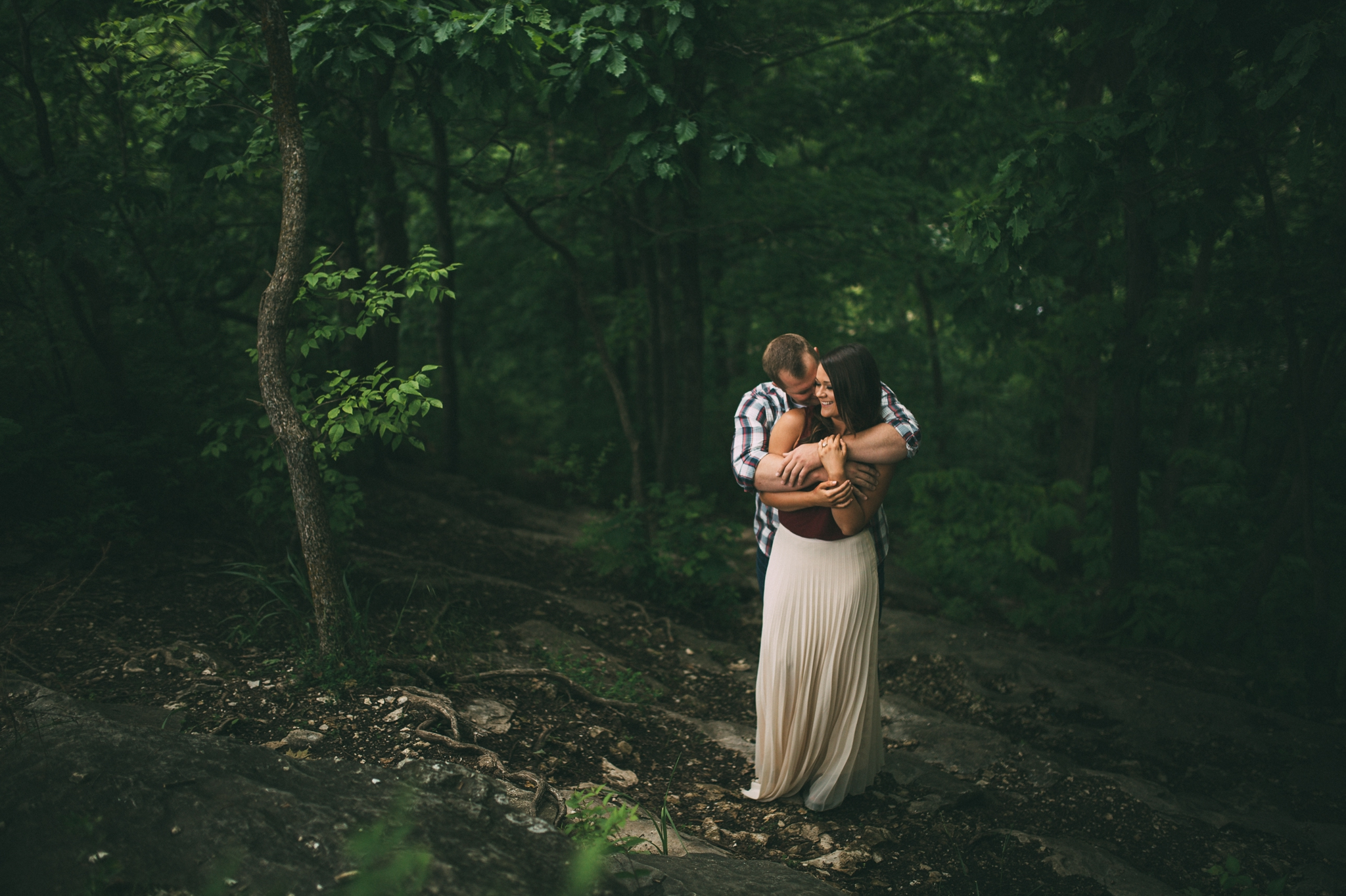 man and woman in nature surrounded by trees on an engagement shoot