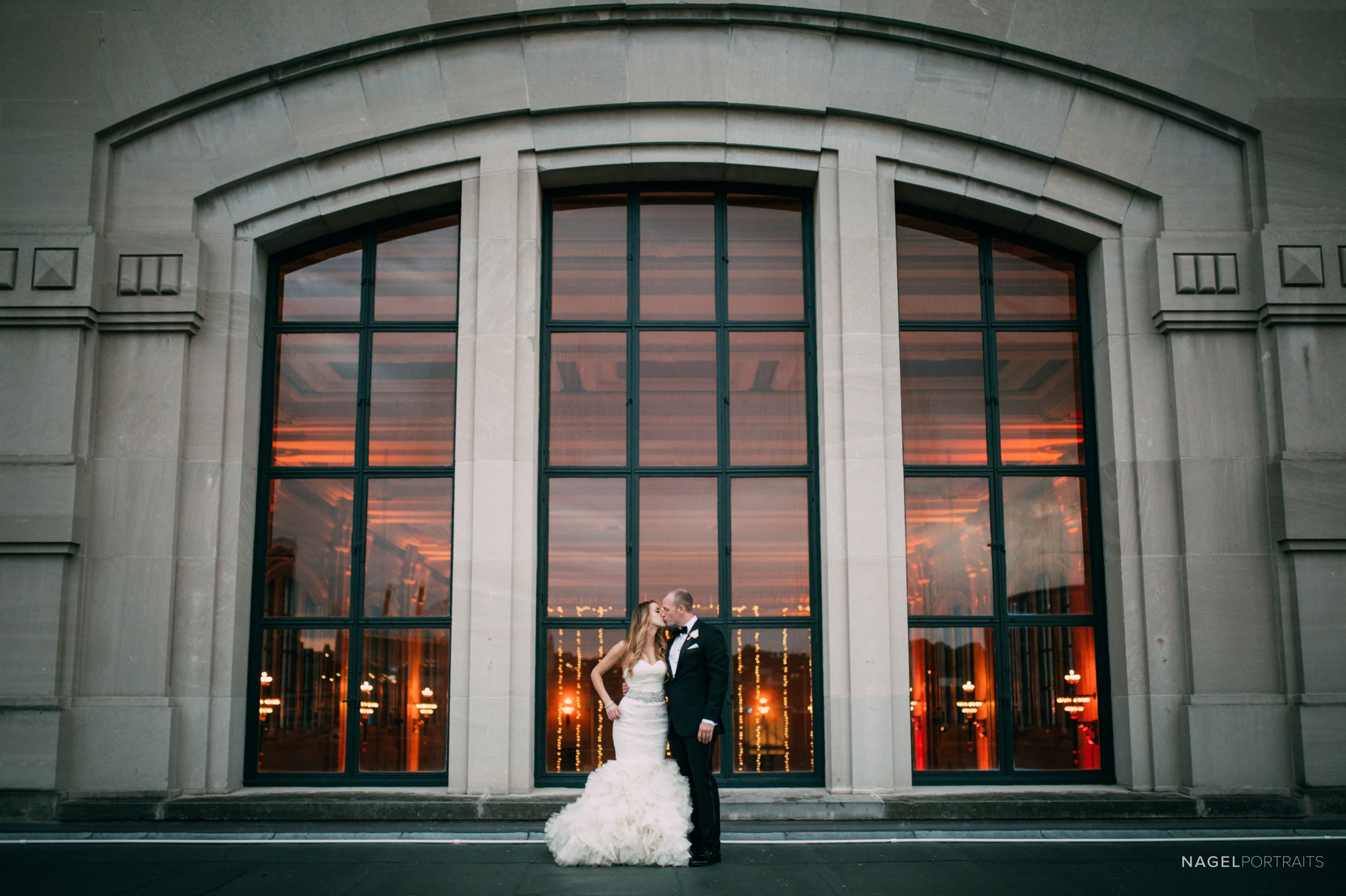 Bride and groom on a rooftop on their wedding day in front of a large window at Union Station