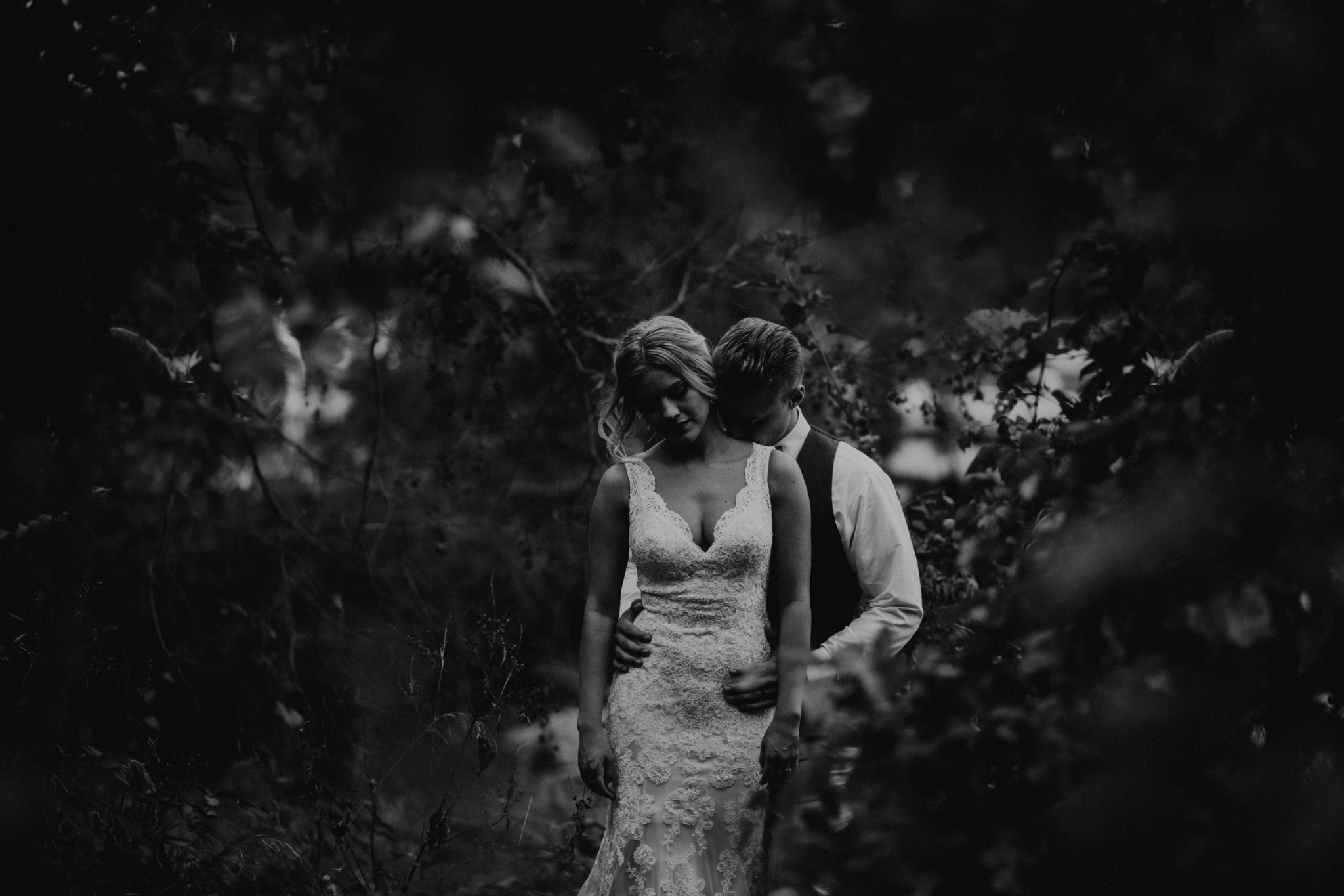 Bride and groom black and white in the woods - dark and moody creative wedding photography