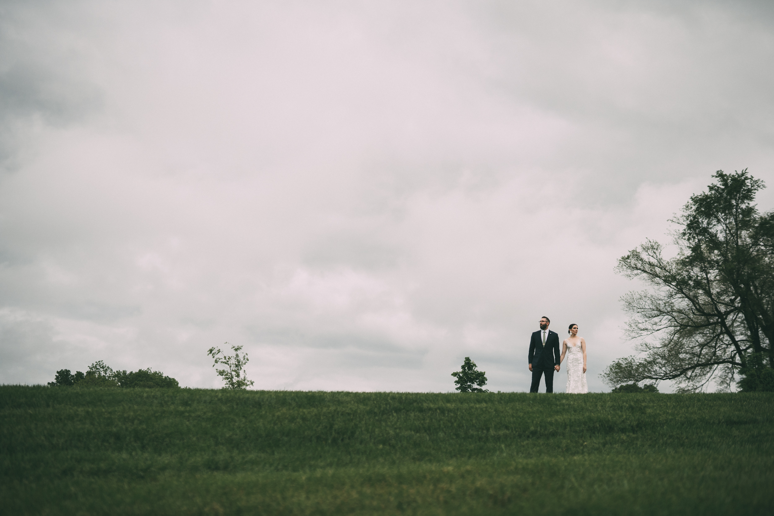 bride and groom standing on the top of a hill in an open field
