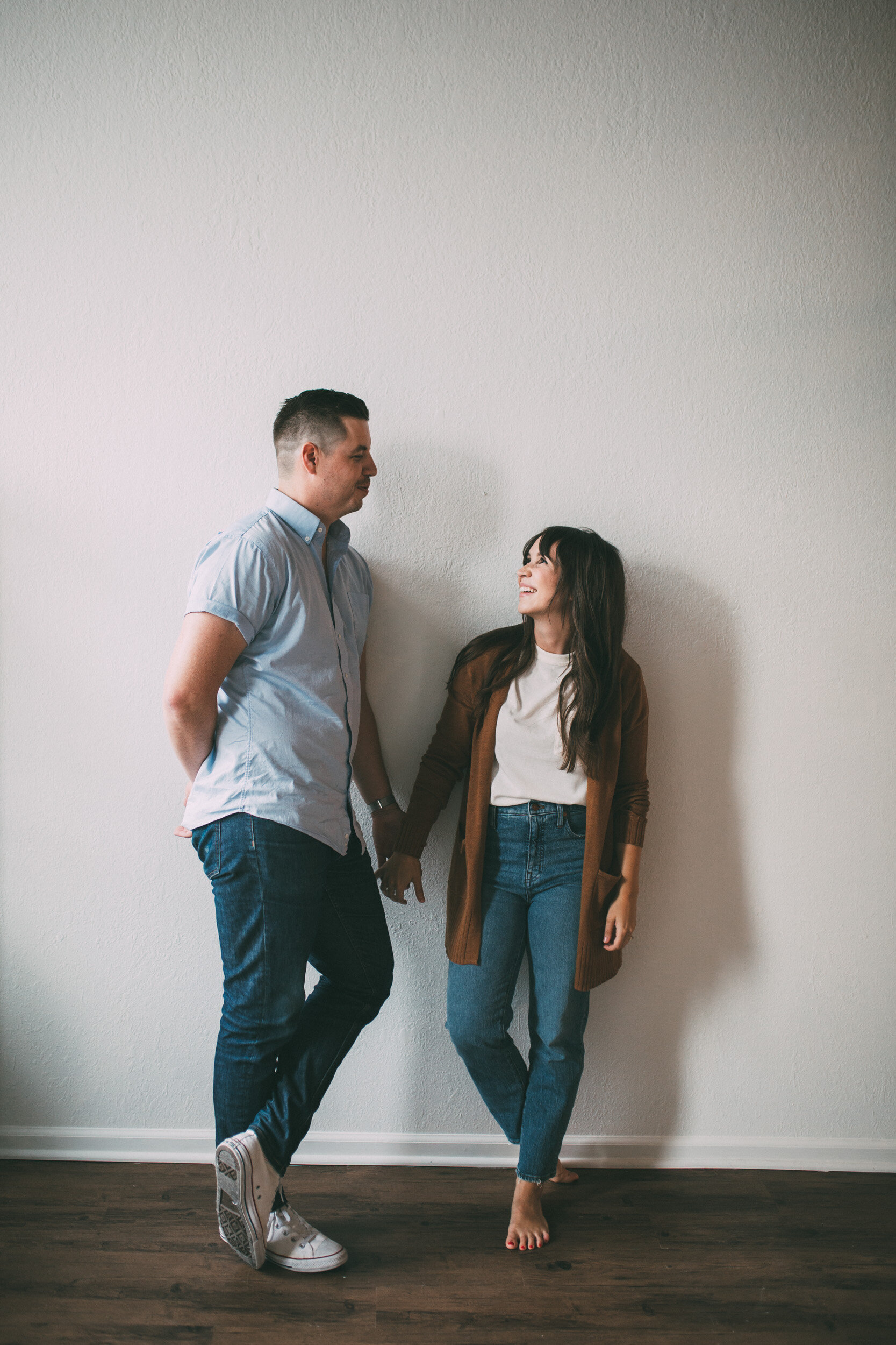 couple standing against white wall smiling