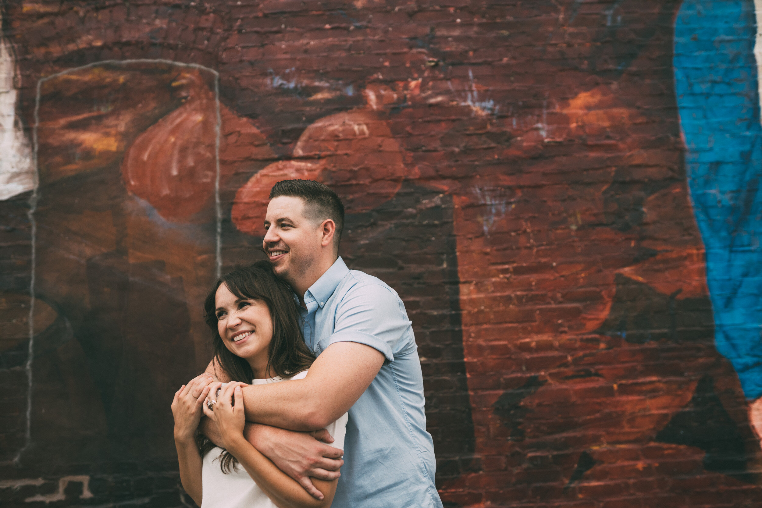 engagement photo in front of wall mural