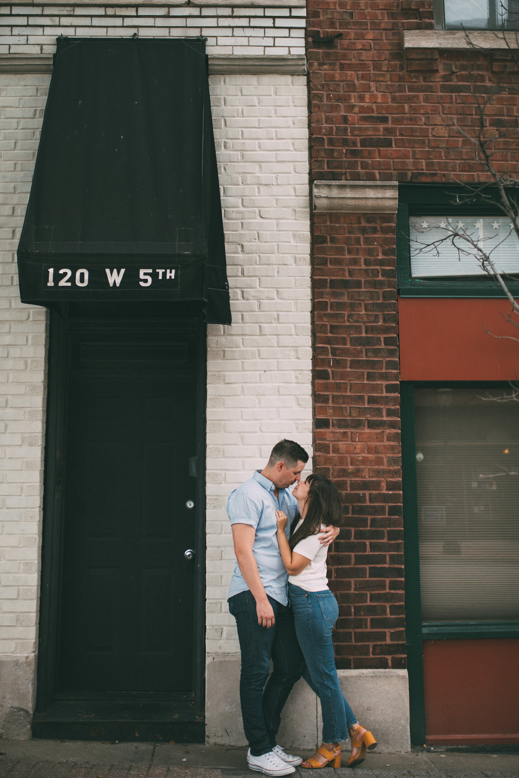 engagement photo on city street in front of brick storefront