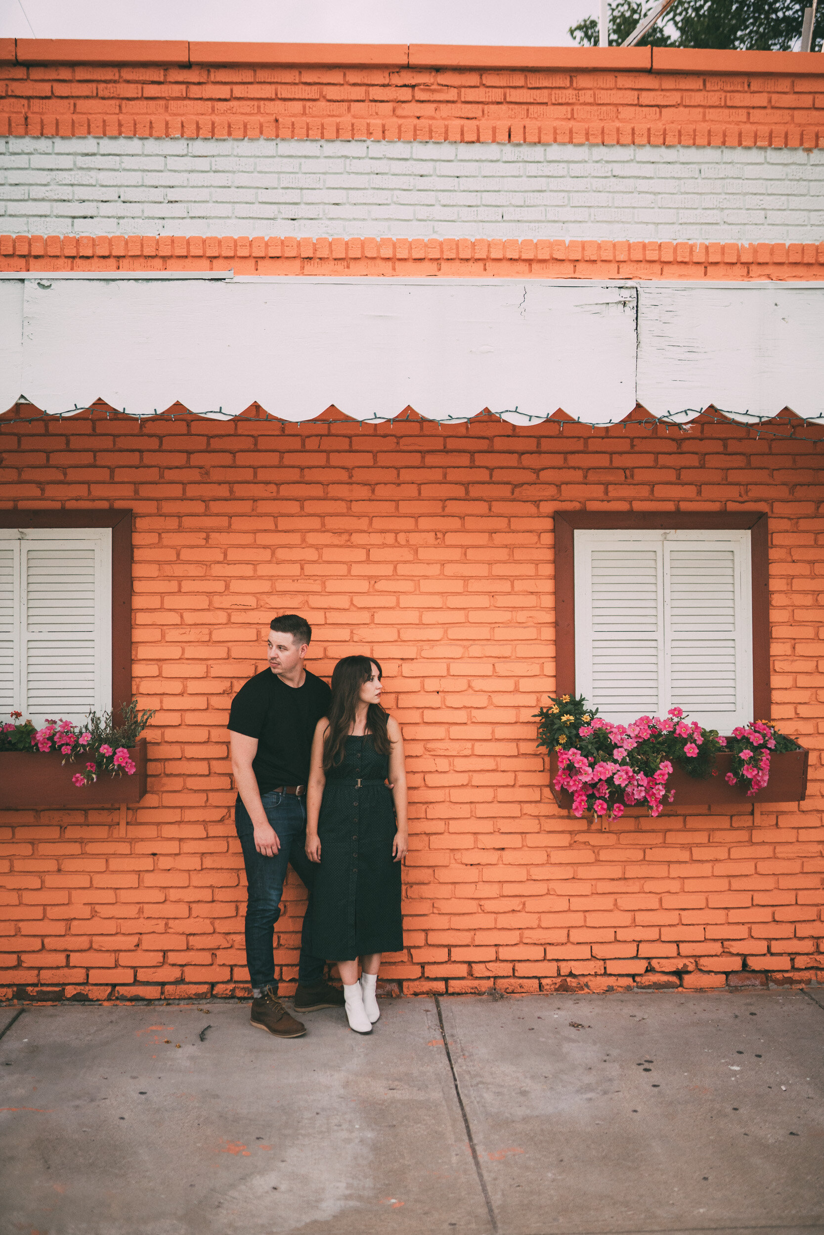 engagement session of couple in front of orange brick building