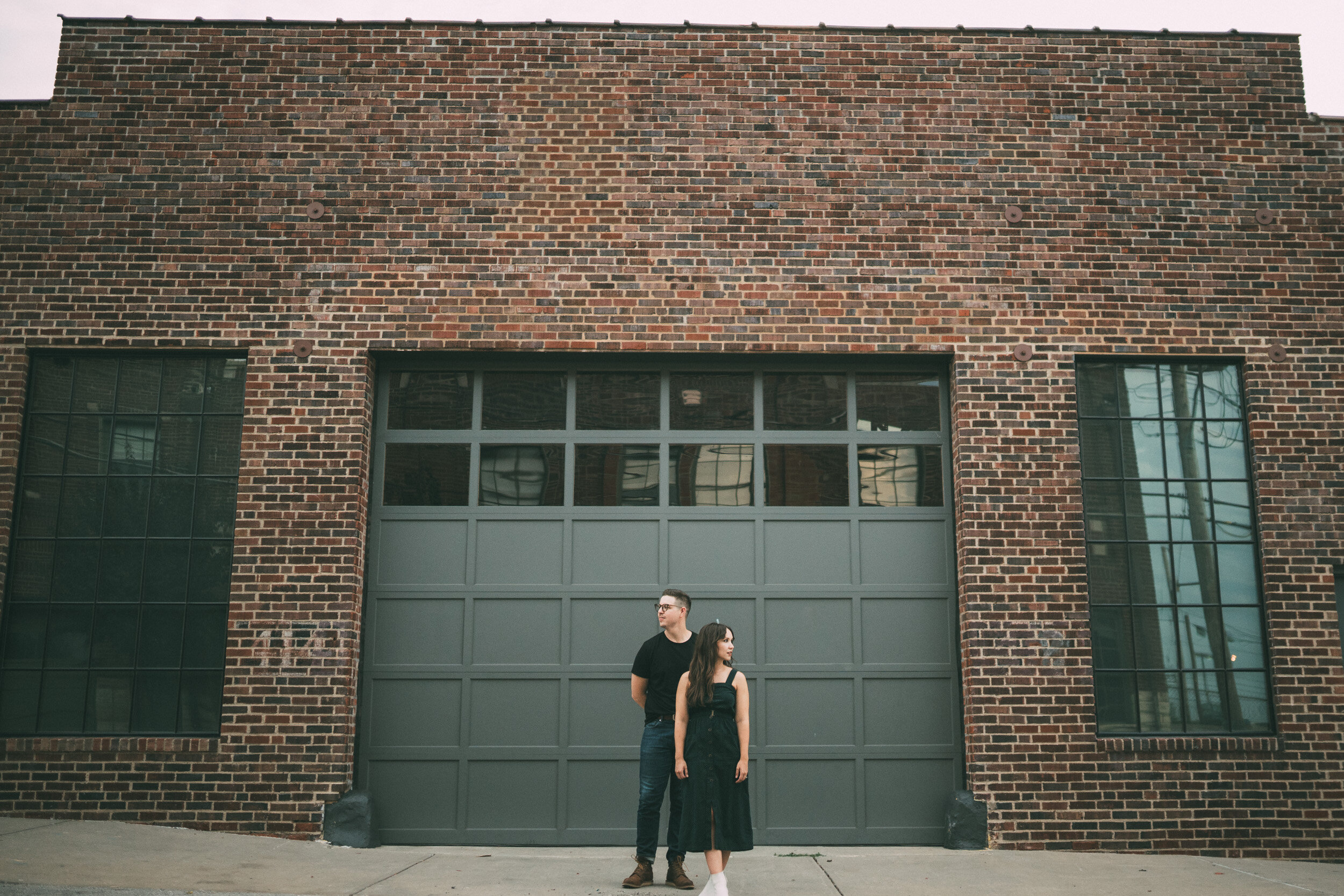 engagement session photos couple in front of garage door in brick building