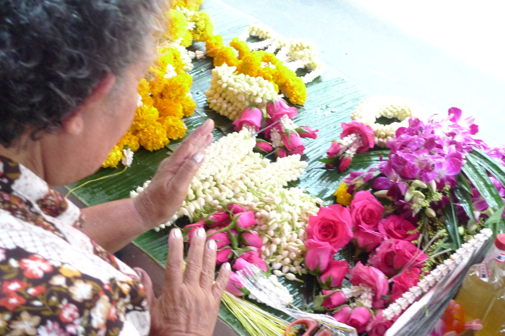 Making Sampaguita Leis in the market. Bangkok, Thailand.