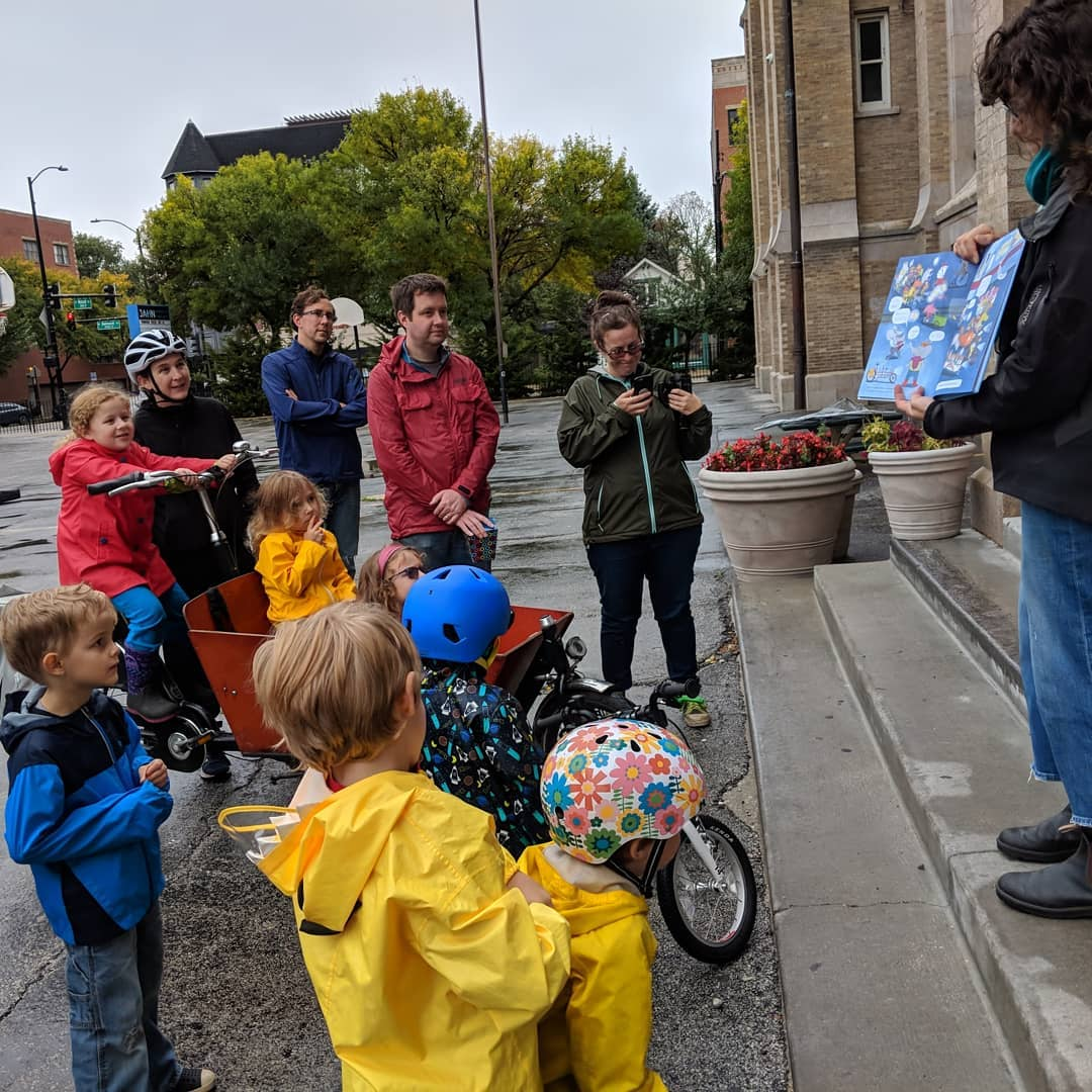 photo credit  Elgin Bike Hub   Here I am reading Cycle City to a very cute Kidical Mass audience! I love when my audience can sit in a box bike!