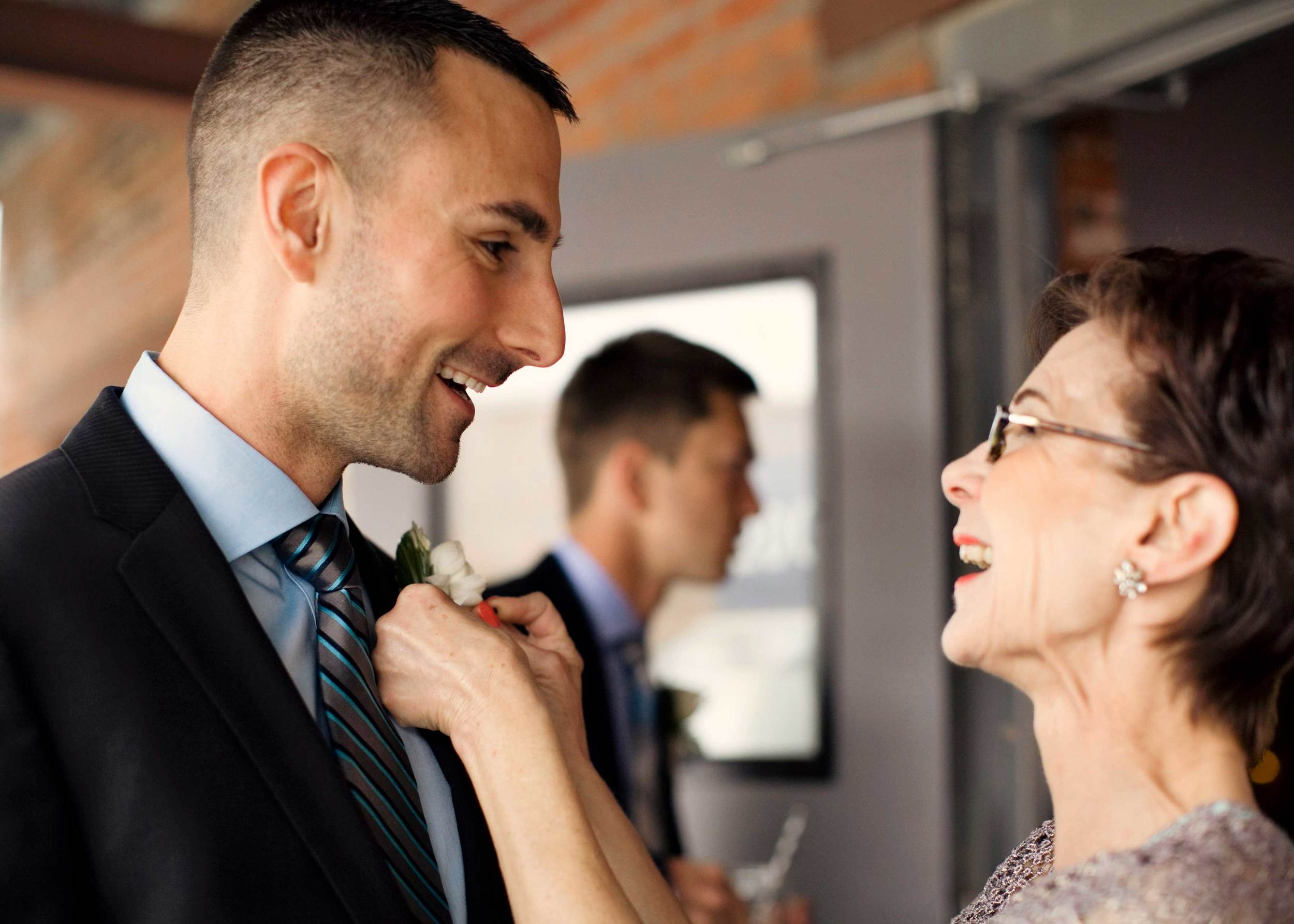 7. MOM & GROOM SHARE SMILES AS SHE PINS ON HIS BOUTONNIERE.