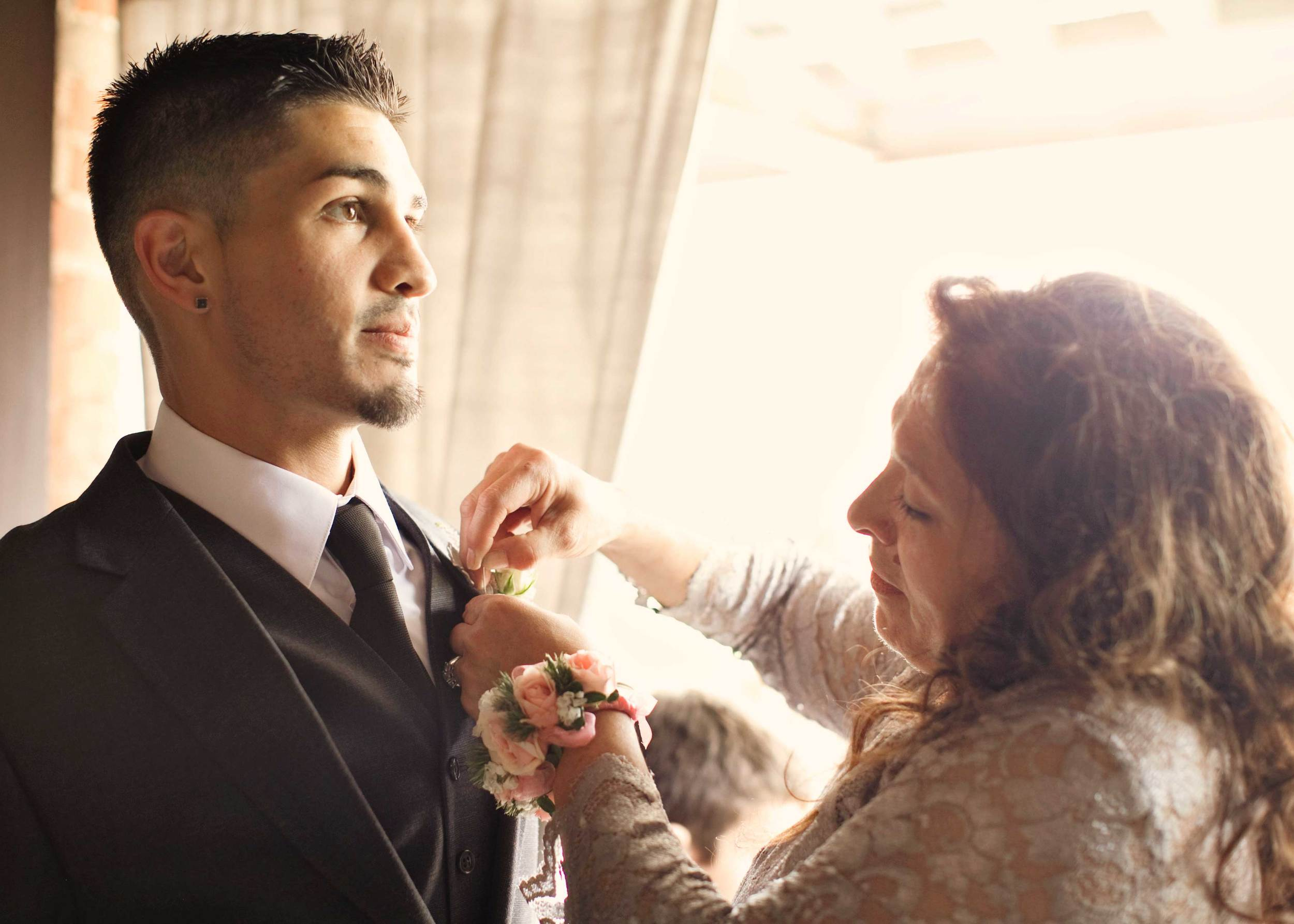 4. OUR GROOM FEELING THE GRAVITY OF THE DAY WHILE MOM PINS ON HIS BOUTONNIERE.