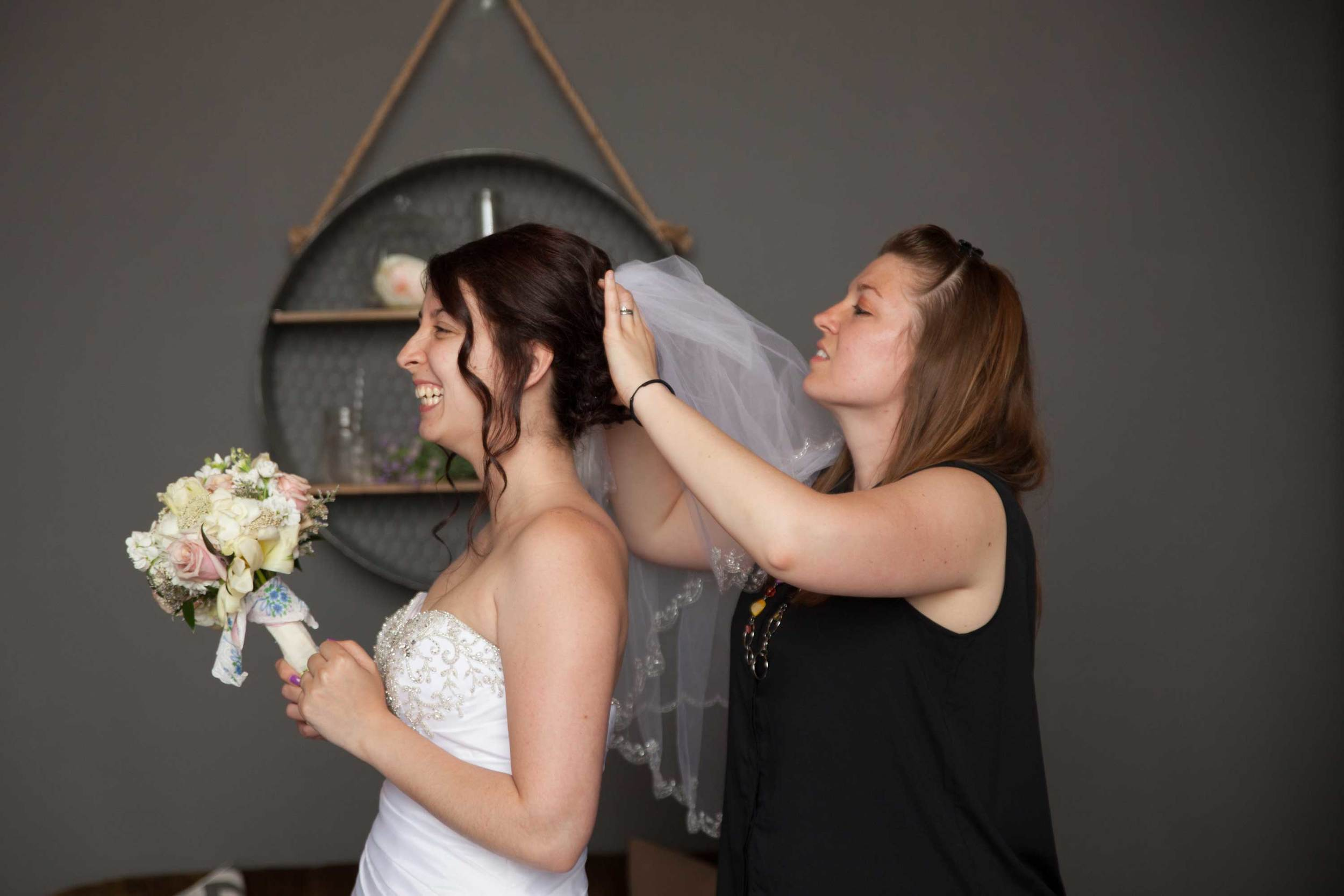 2. BIG GIGGLES WHILE OUR BRIDE'S ASSISTANT PINS IN THE VEIL...