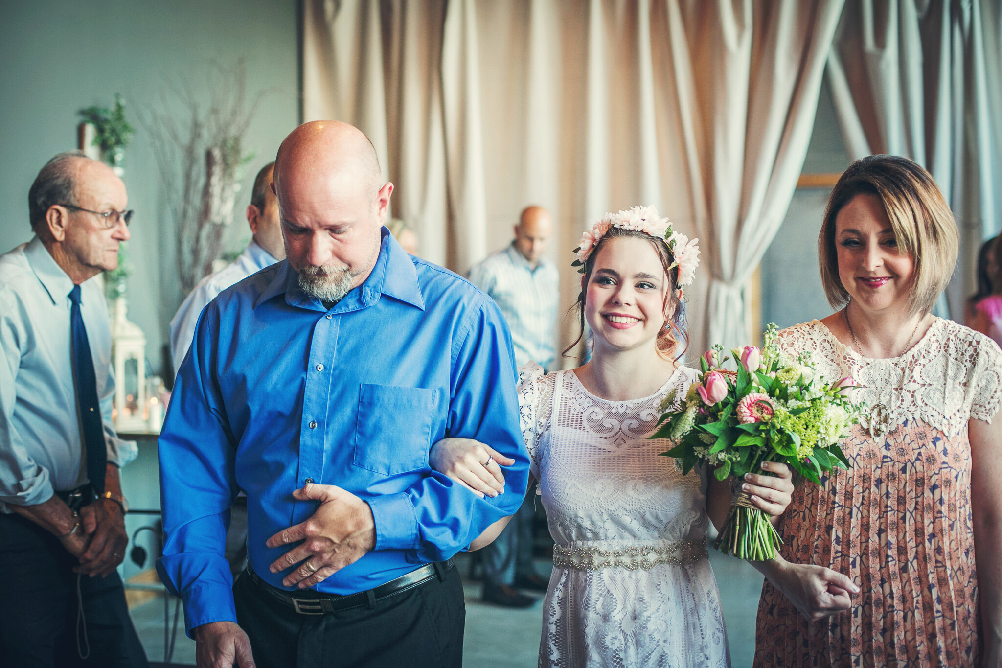 Little lovebird, Sophie, is covered in flowers from head to toe as she is escorted down the aisle by both her mother and father!