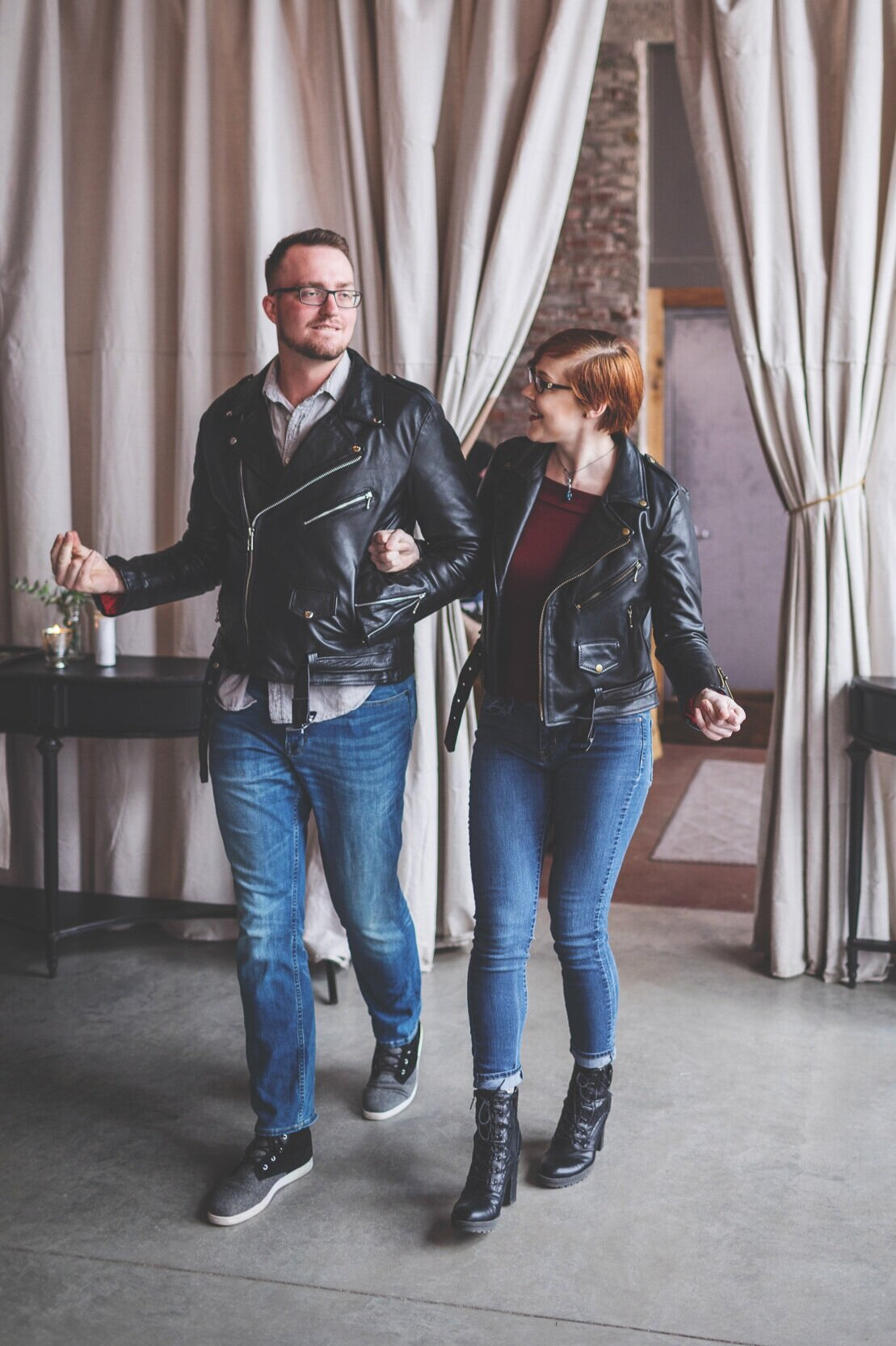 "Leather jacket lovers, Kati & Dustin, rock their way down the aisle, hand-in-hand, before saying ""I do""."