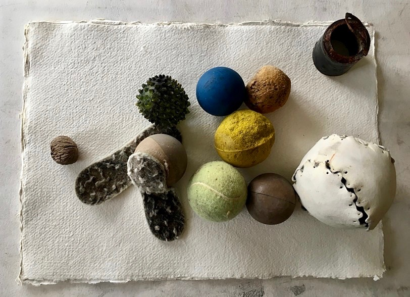 Collection of rounded objects including various balls and one walnut found in rocks surrounding Governors Island.