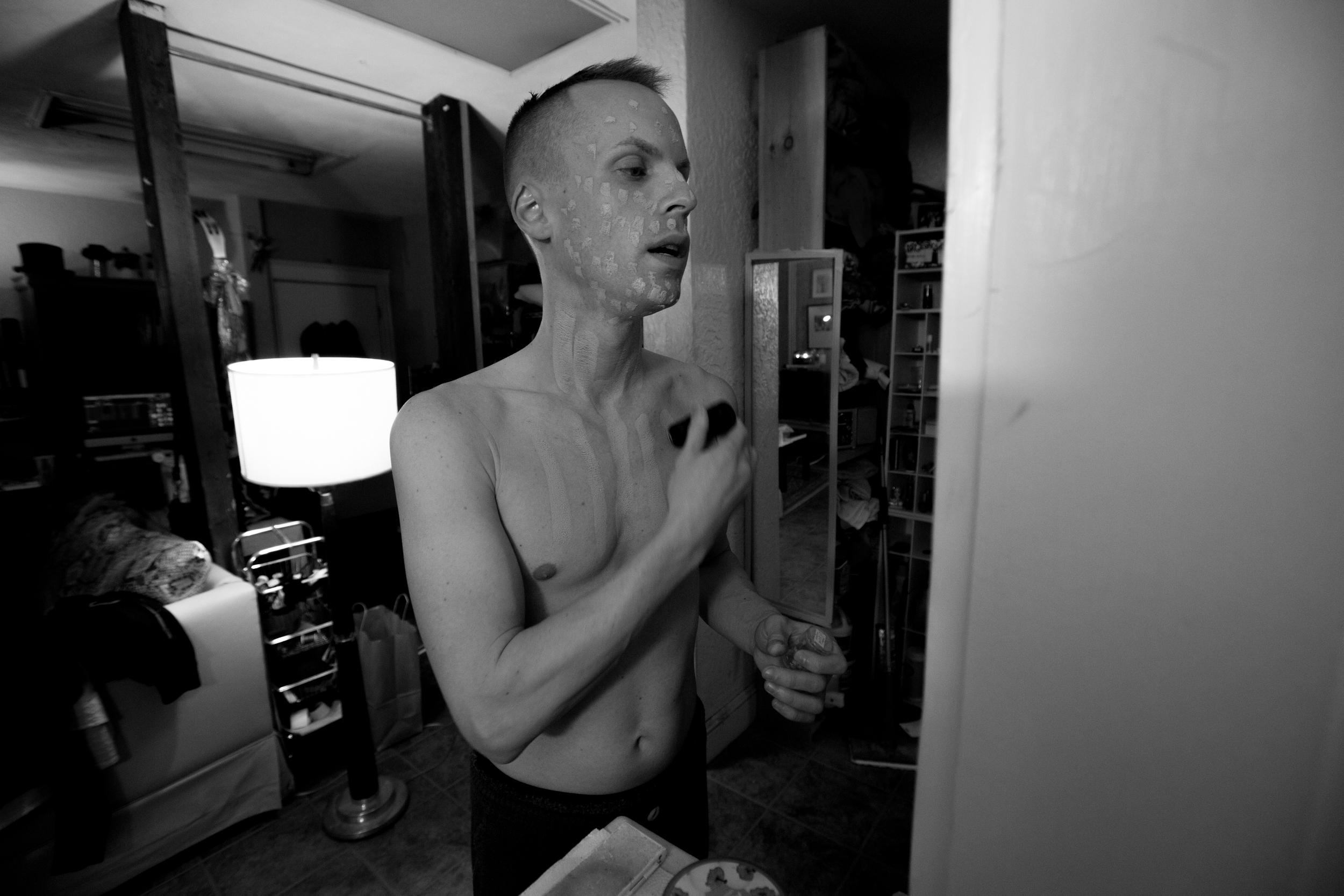 """Brian McCook applies makeup to his chest and face in his Broadway Street apartment in Boston, Mass. while preparing to cross-dress for a performance at Jaque's, a bar in Boston that features dancers in drag. """"I've been dressing like a girl since I was three,"""" McCook said. Photo credit: Justin Saglio."""