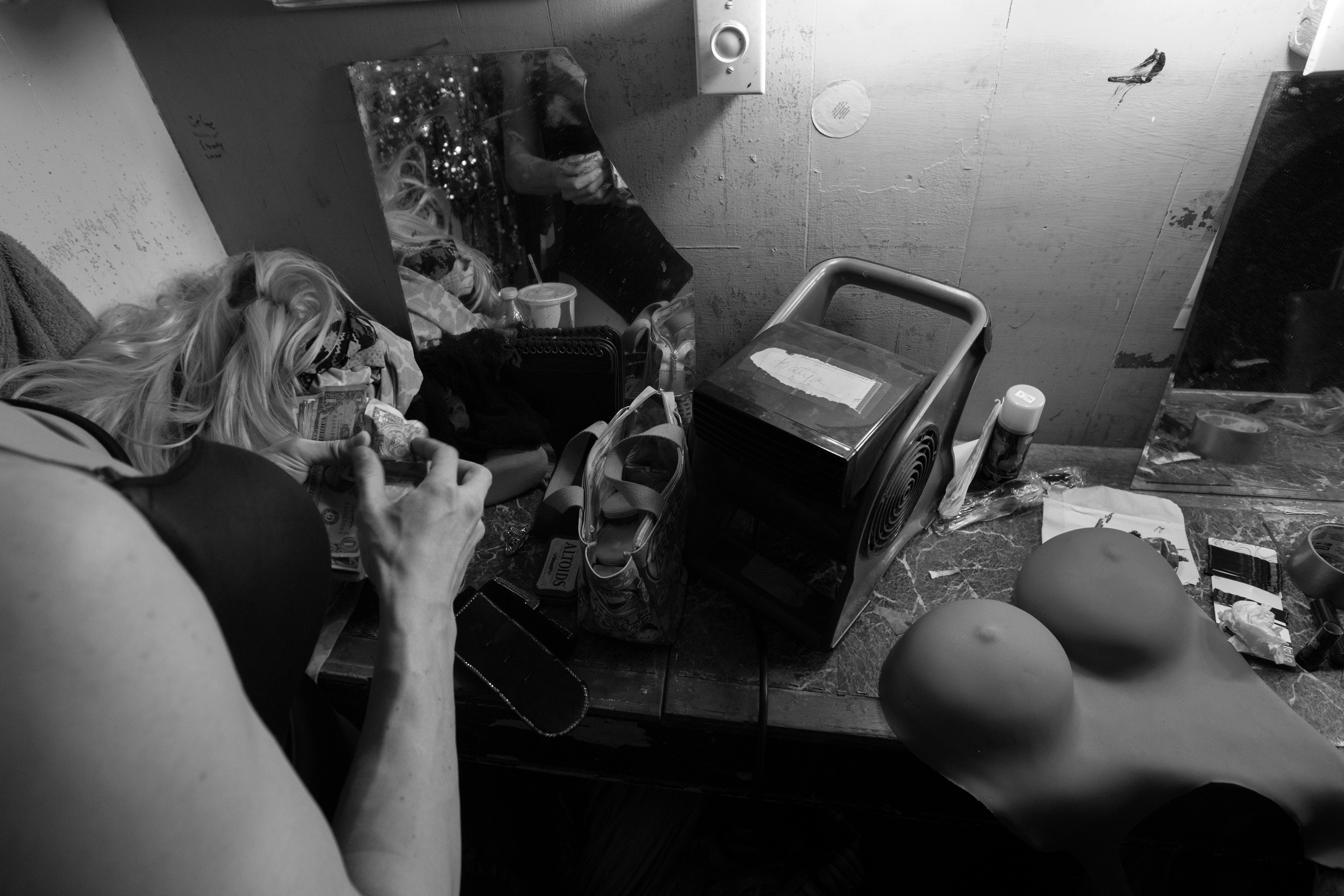 """Brian McCook counts dollar bills given to him as tips during his performance at Jaque's, a bar on Broadway Street in Boston, Mass. that features performers in drag. """"I'm always trying to get better,"""" McCook said. """"I don't want my shows to fizzle out."""" Photo credit: Justin Saglio"""