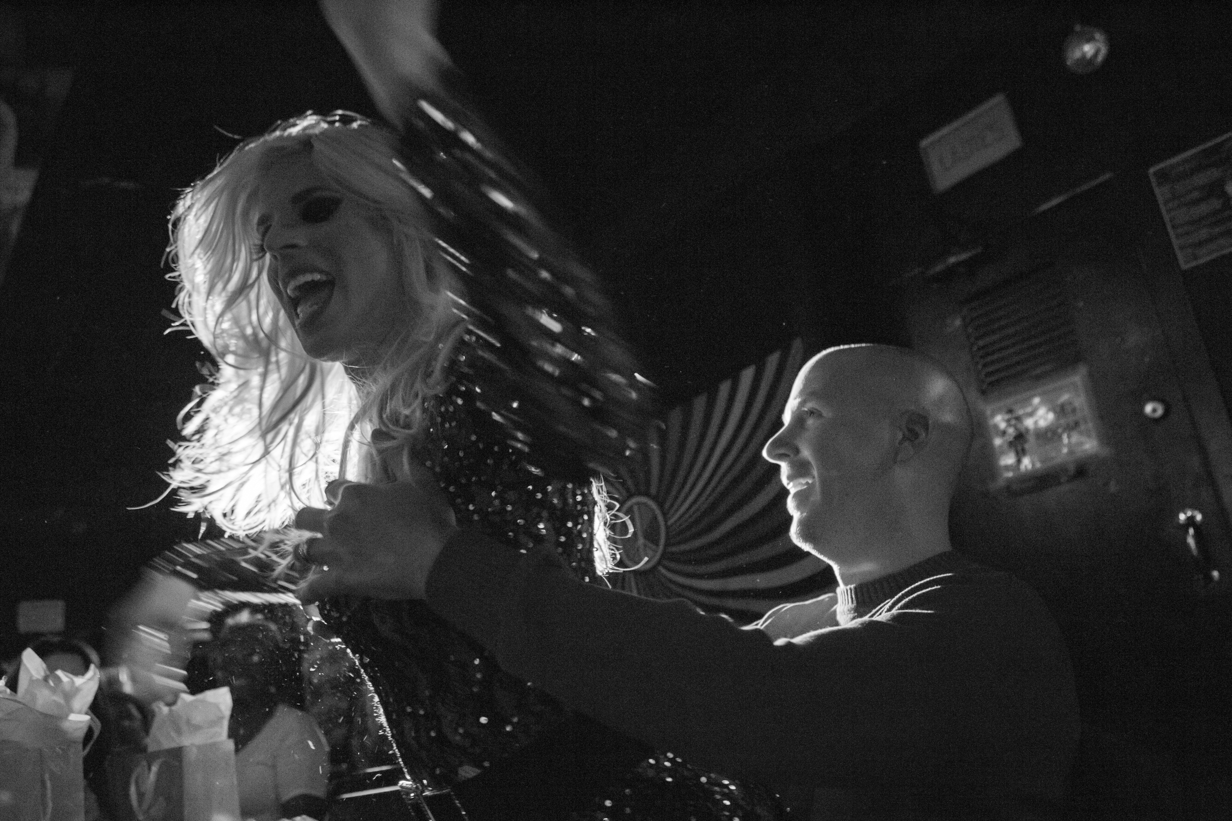 An event attendee at Jaque's, a bar on Broadway Street in Boston, Mass., reacts as Brian McCook sits on his lap during a performance that featured dancers in drag. Photo credit: Justin Saglio
