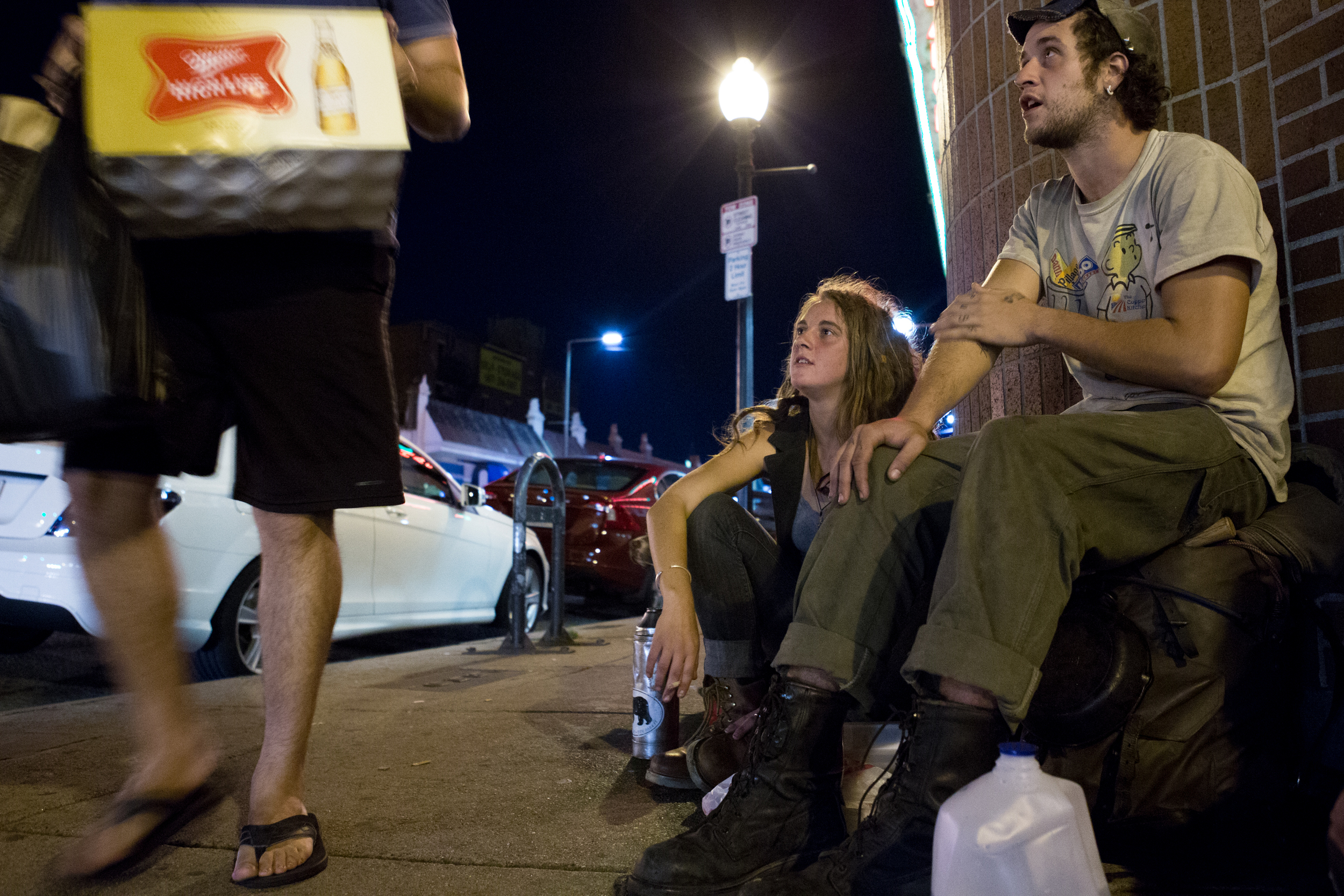 """Two homeless 20-year-olds who asked to be identified as Toby (left) and Anchor (right) ask a pedestrian for one of his beers outside Blanchard's liquor store in Allston. """"We don't do drugs or anything, we're just alcoholics,"""" Anchor said.   Photo credit: Justin Saglio"""
