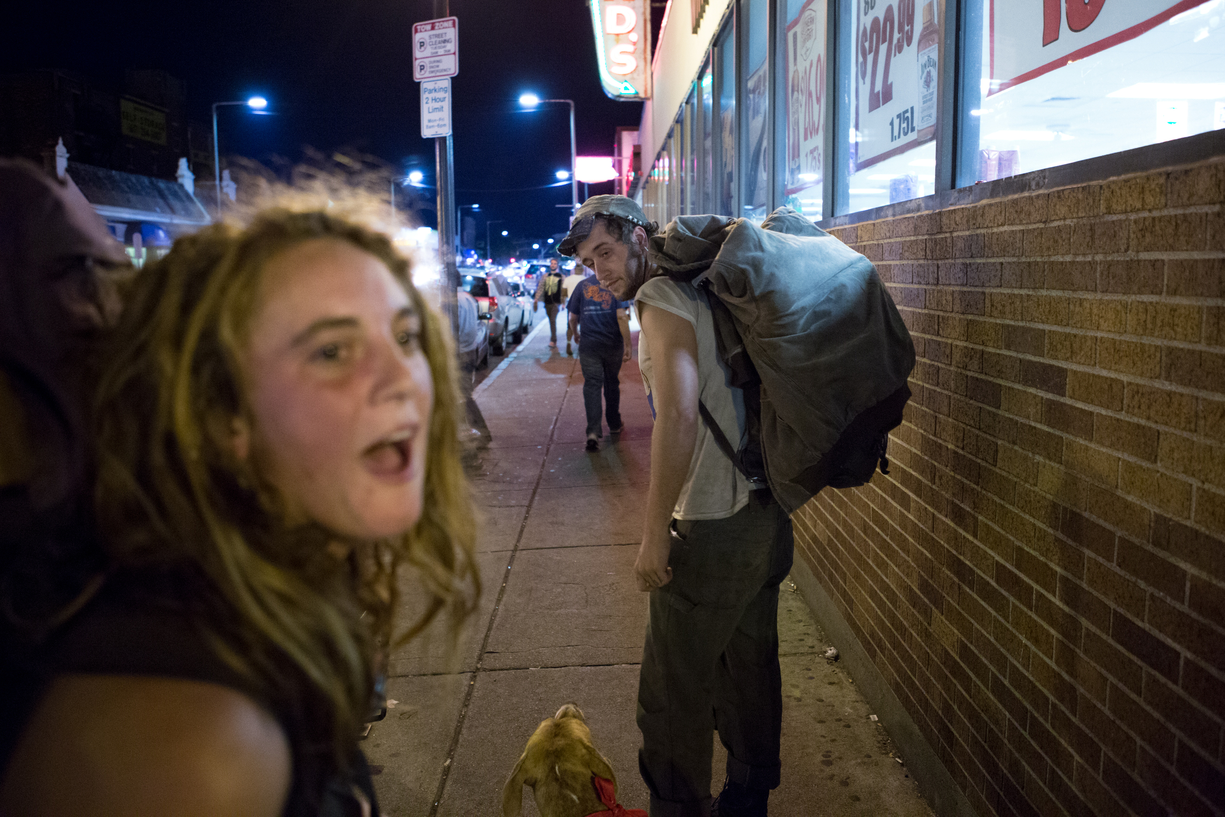 """Two 20-year-old homeless people who asked to be identified as Toby (left) and Anchor (right) depart the location where they had been asking pedestrians for money and alcohol outside Blanchard's liquor store in Allston after police asked them to leave. """"I ran away at 13,"""" Anchor said. """"Probably because my mom wanted me to do dishes."""" Photo credit: Justin Saglio"""