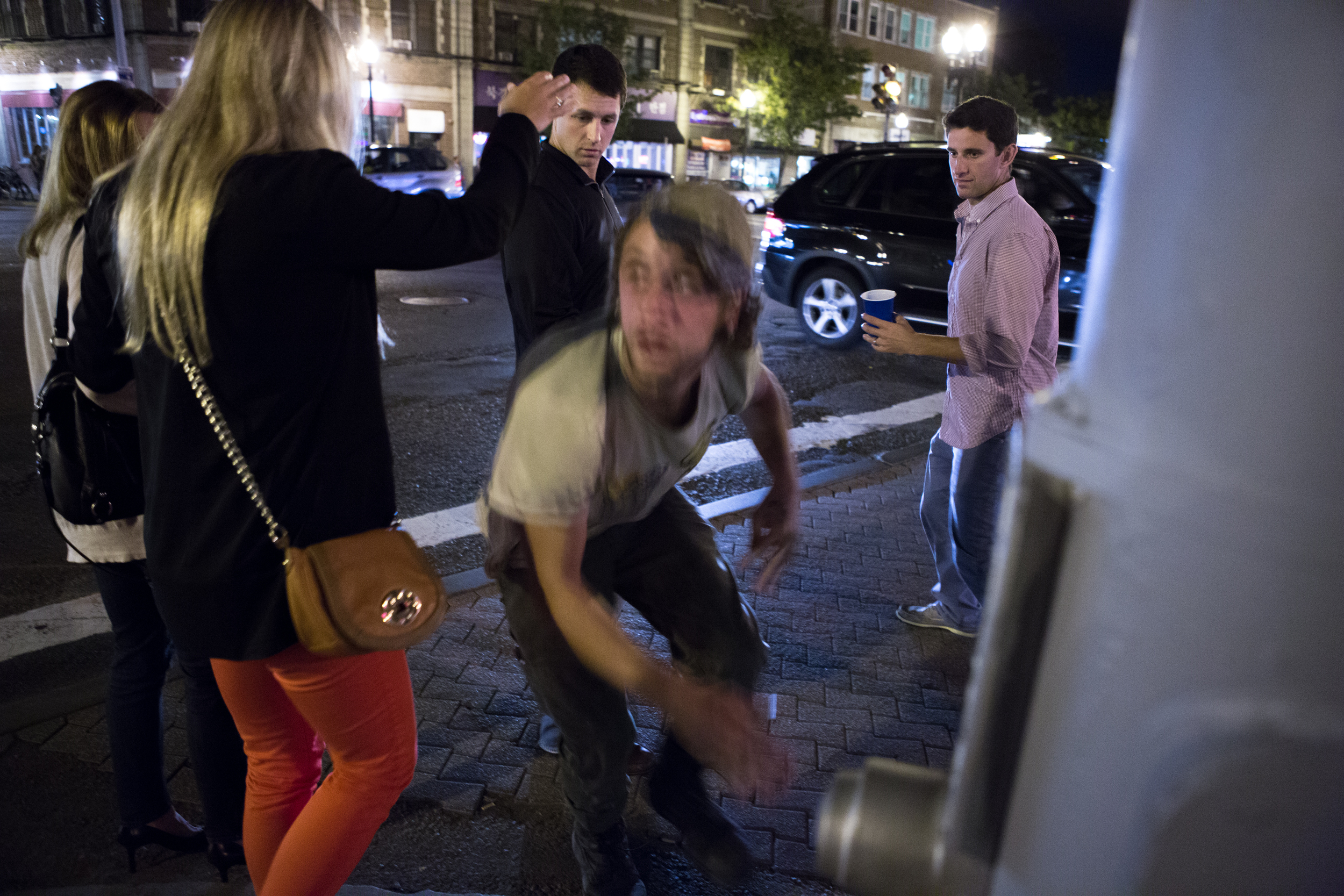 """A 20-year-old homeless man who asked to be identified as Anchor leaps upward in a crowd of pedestrians, scaring them, after crawling on the ground to get in position outside Blanchard's liquor store in Allston. """"People give us dirty looks but at least I don't have to go to a job,"""" Anchor said. Photo credit: Justin Saglio"""