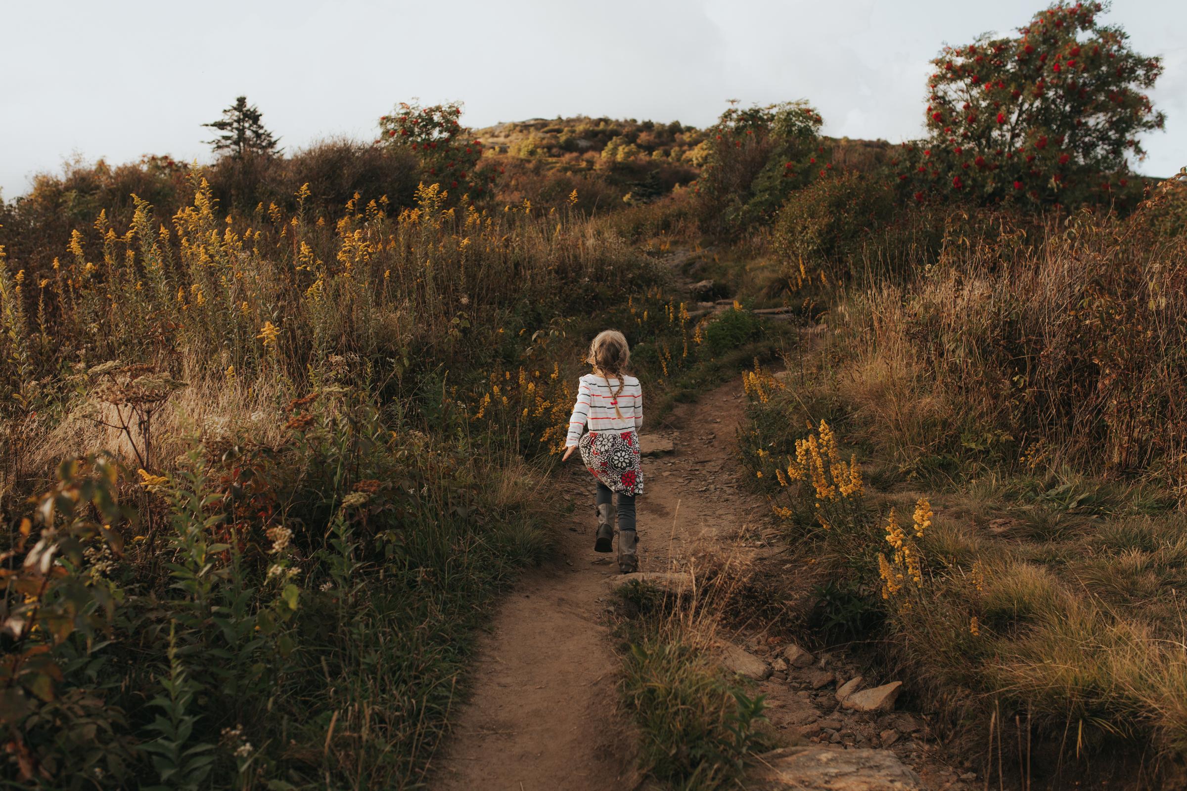 Girl runs through field on Blue Ridge parkway