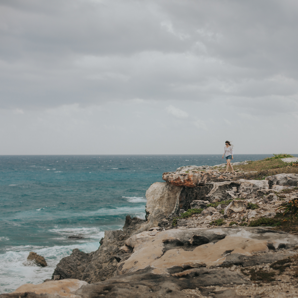 Woman strolls along the coast of Punta Sur in Isla Mujeres, Mexico.