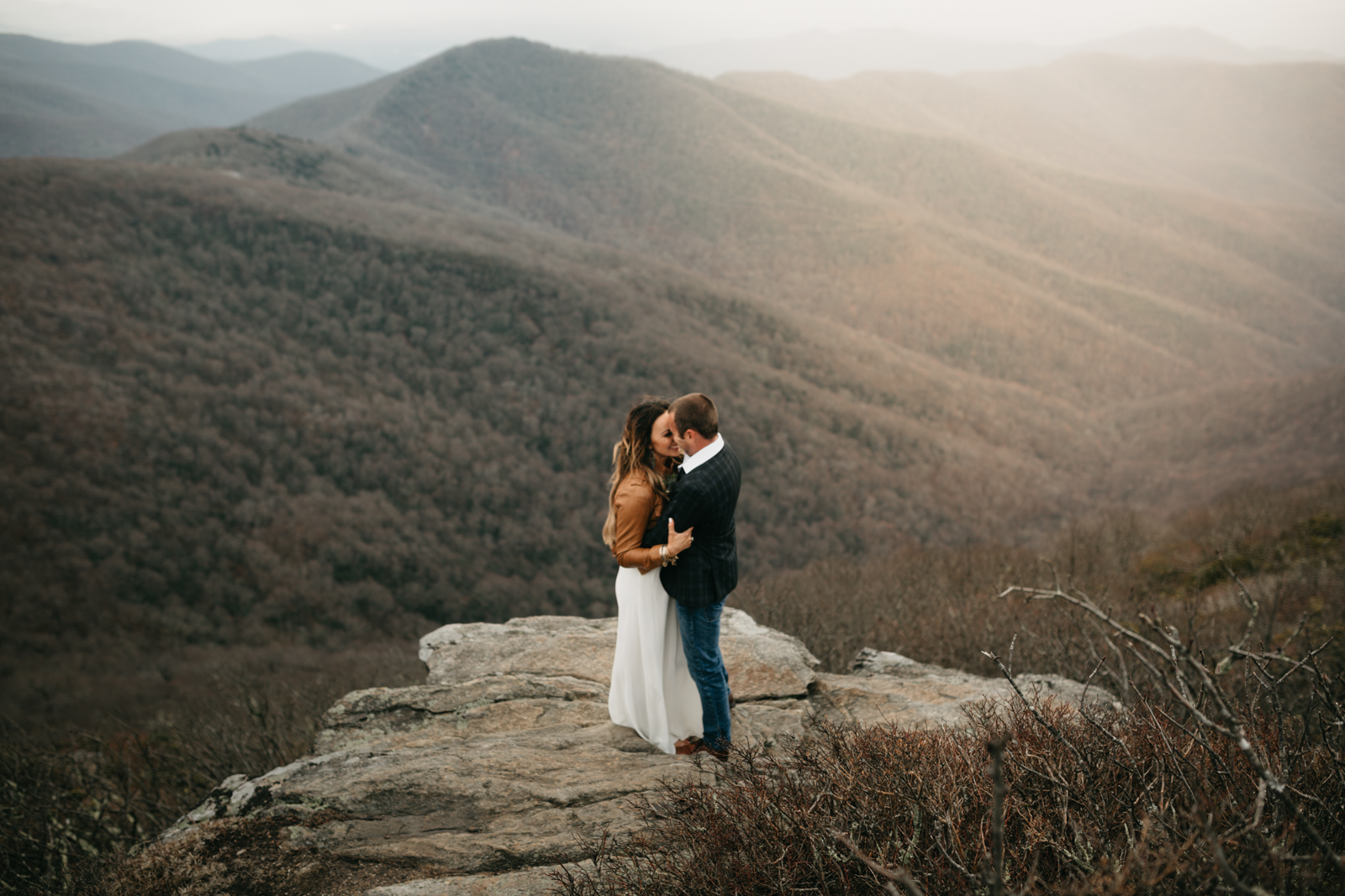 Newly married bride and groom on the rock overlook on Craggy mountain in Asheville, North Carolina.