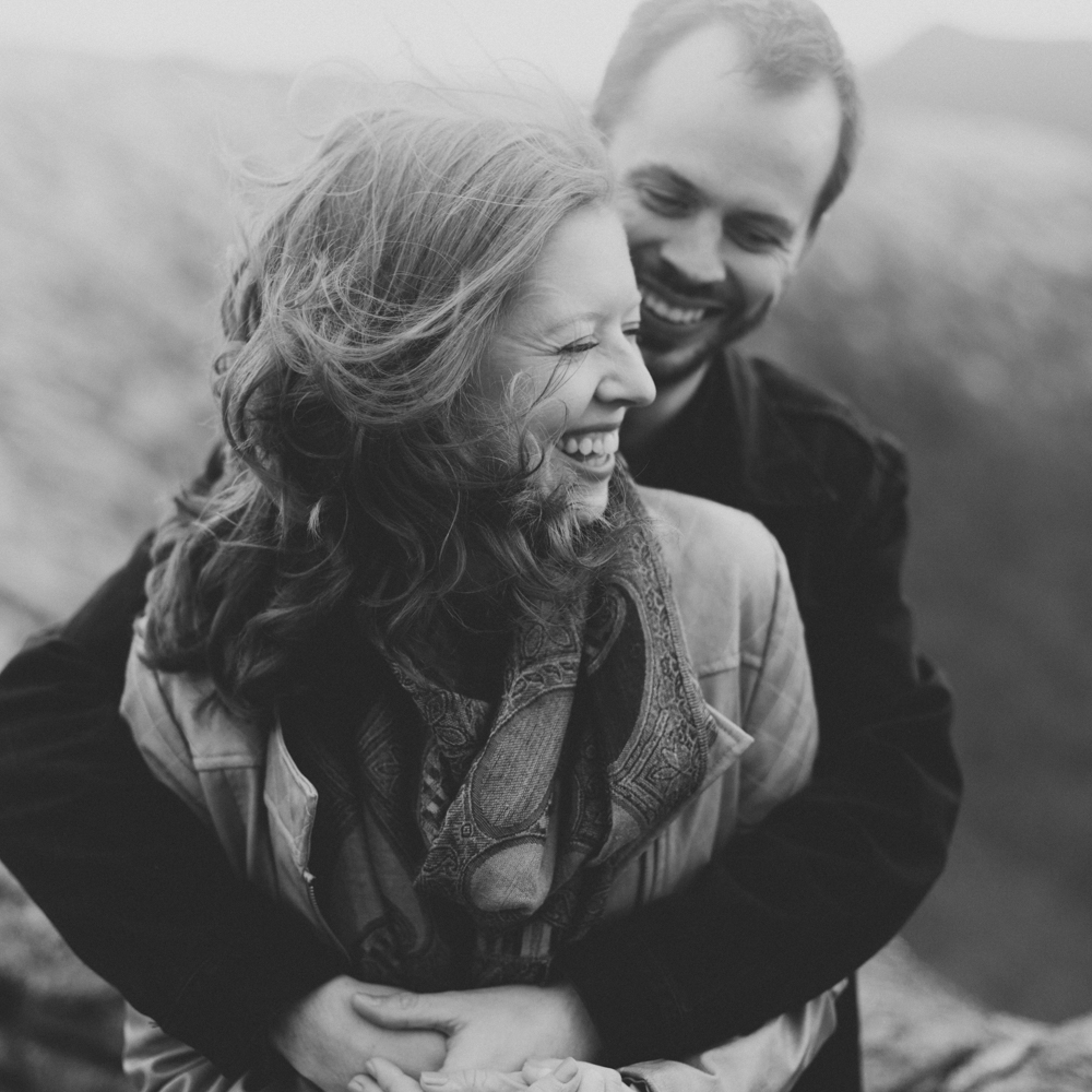 Couple embraces during a winter photo shoot on top of Craggy Pinnacle.