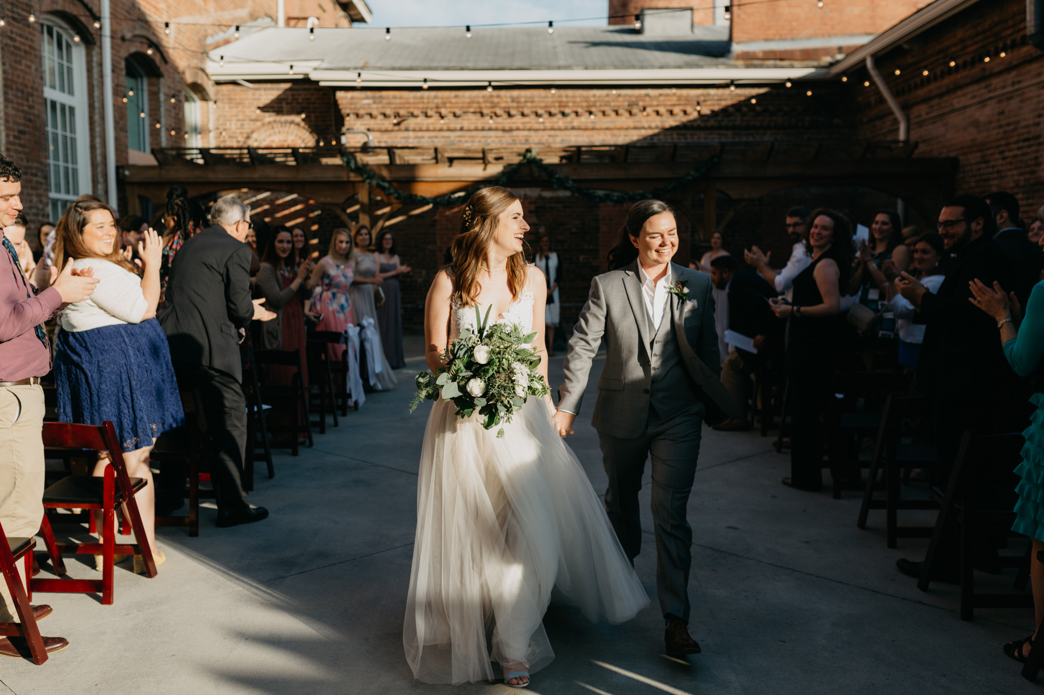Newly married couple joyously walks out of their wedding ceremony.