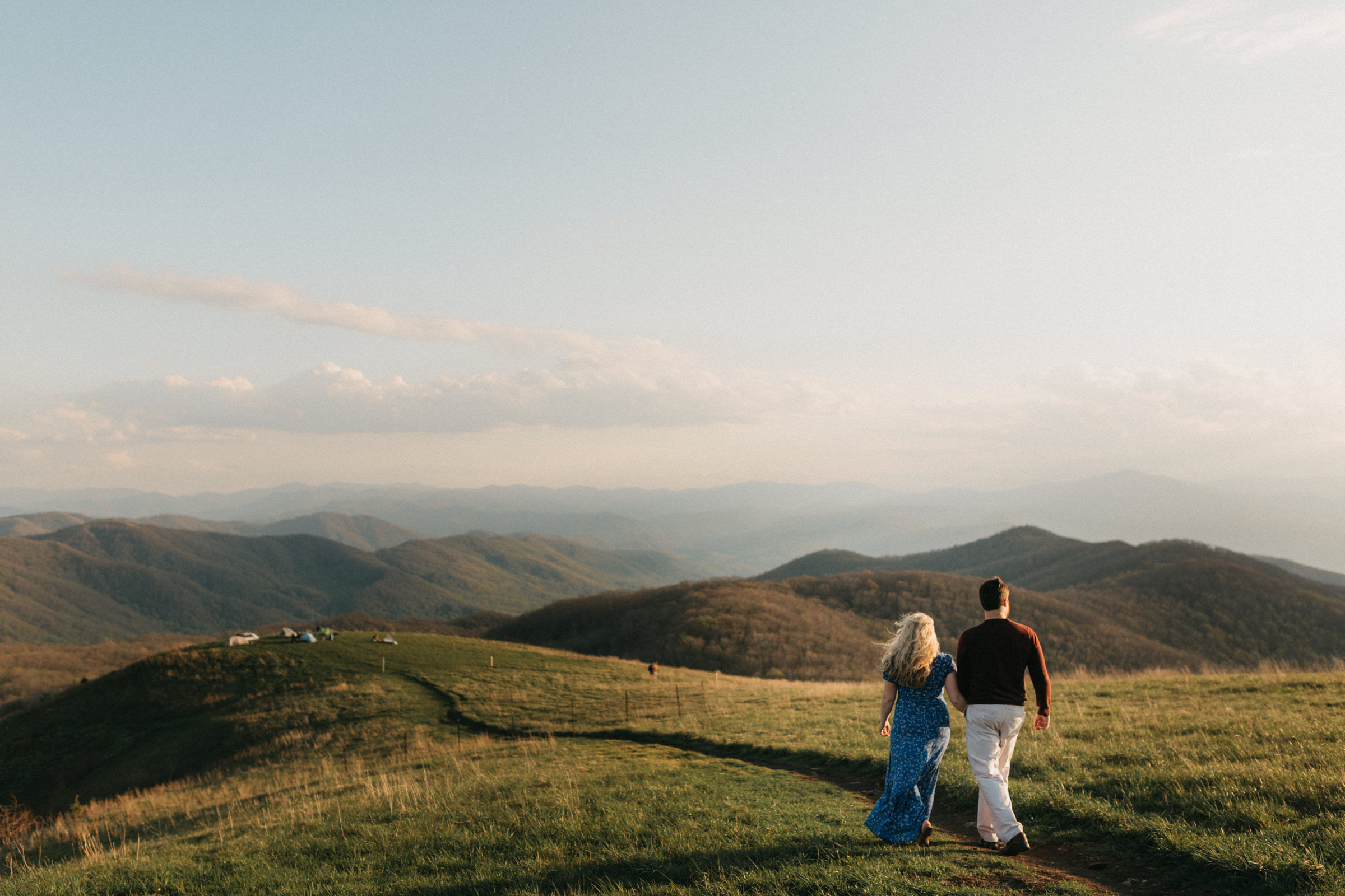 Couple walking along the Appalachian trail at sunset on Max Patch Mountain.