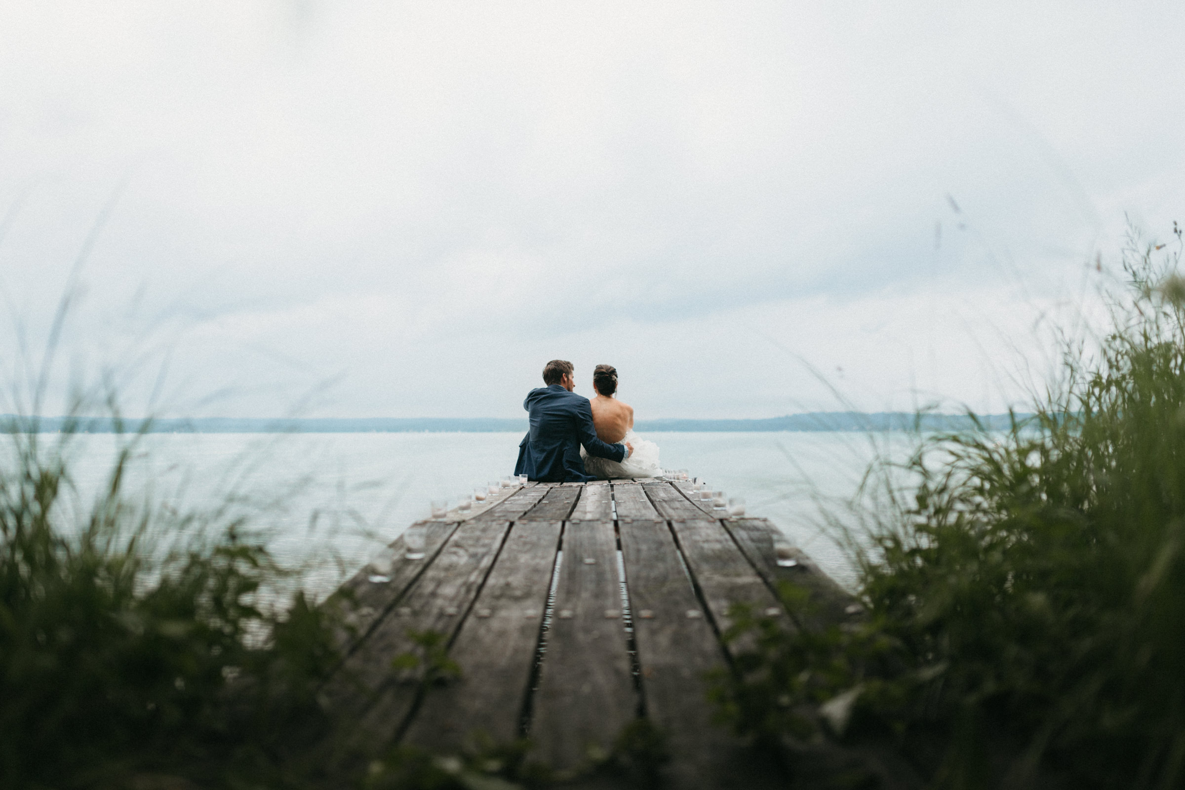 Couple sits on a dock of Elk Lake after just getting married.