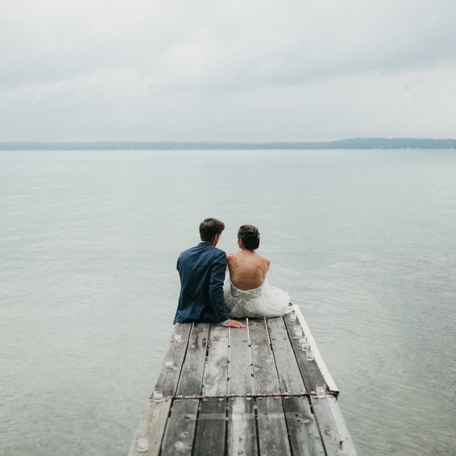 Bride and groom on a dock on Elk Lake, Michigan.