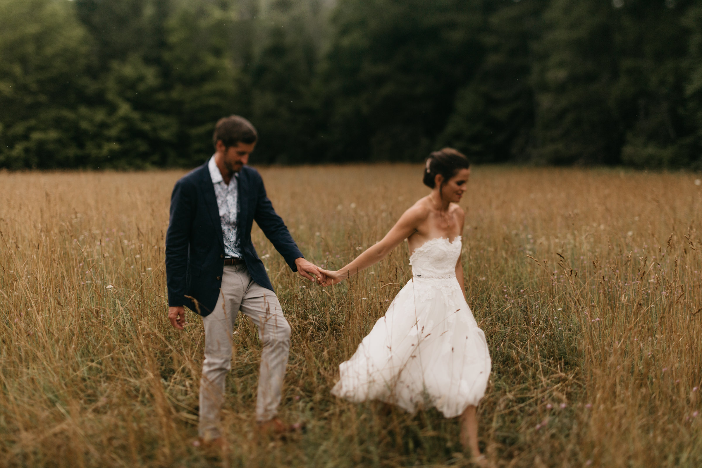 Newlywed bride and groom walk through a tall field of grass in northern Michigan in July.