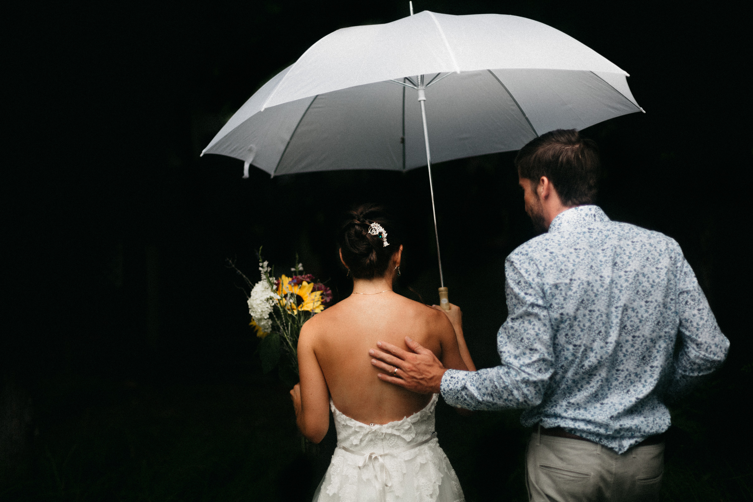 Couple walks through the rain with an umbrella after just getting married in Traverse City, Michigan.