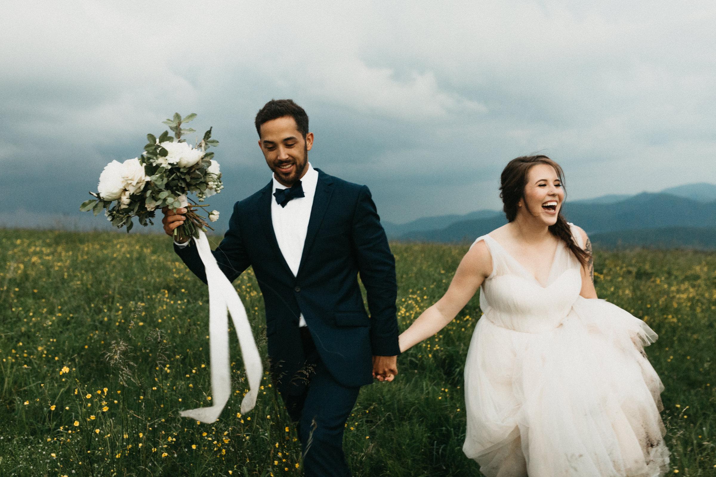 Newlyweds walk through high grass on the Appalachian trail after their wedding.