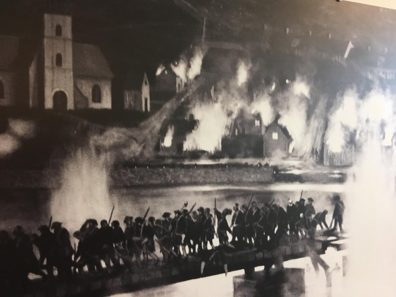 """Haldensere brenner ned sin egen by for å jage ut de svenske okkupantene. Maleriet """"Fredrikshald 4. juli 1716"""" av Mark Postlethwaite."""
