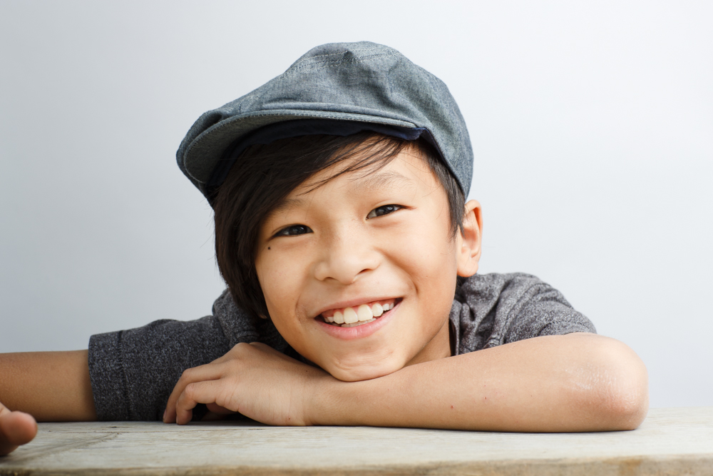 Portrait of boy smiling in hat - Ryan Pavlovich