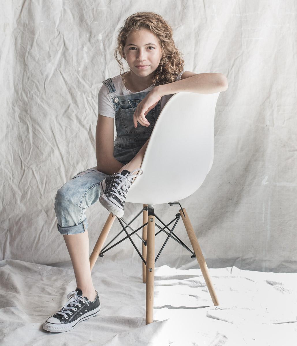 Teen girl in chair by Ryan Pavlovich Photography