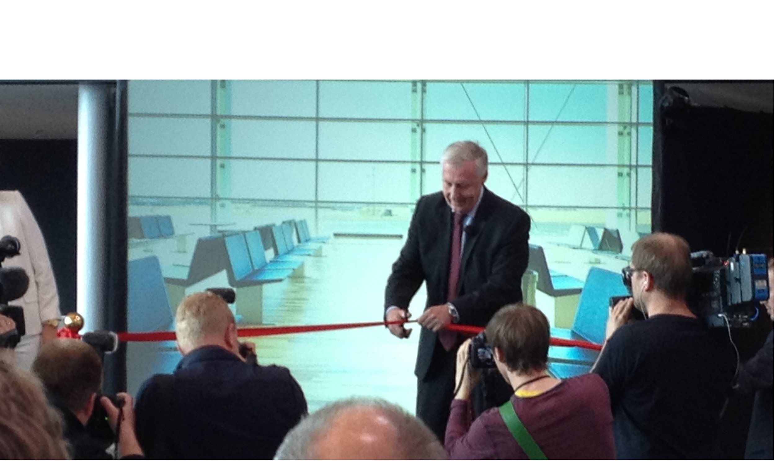 The official opening of the renovation and expansion of Aalborg Airport May 29th 2013. The Minister of Transport, Henrik Dam Kristensen, cuts the red band.  Marcus Pedersen ApS has - in cooperation with Thorsøe & Fasting and GPD - designed and developed the new interior.