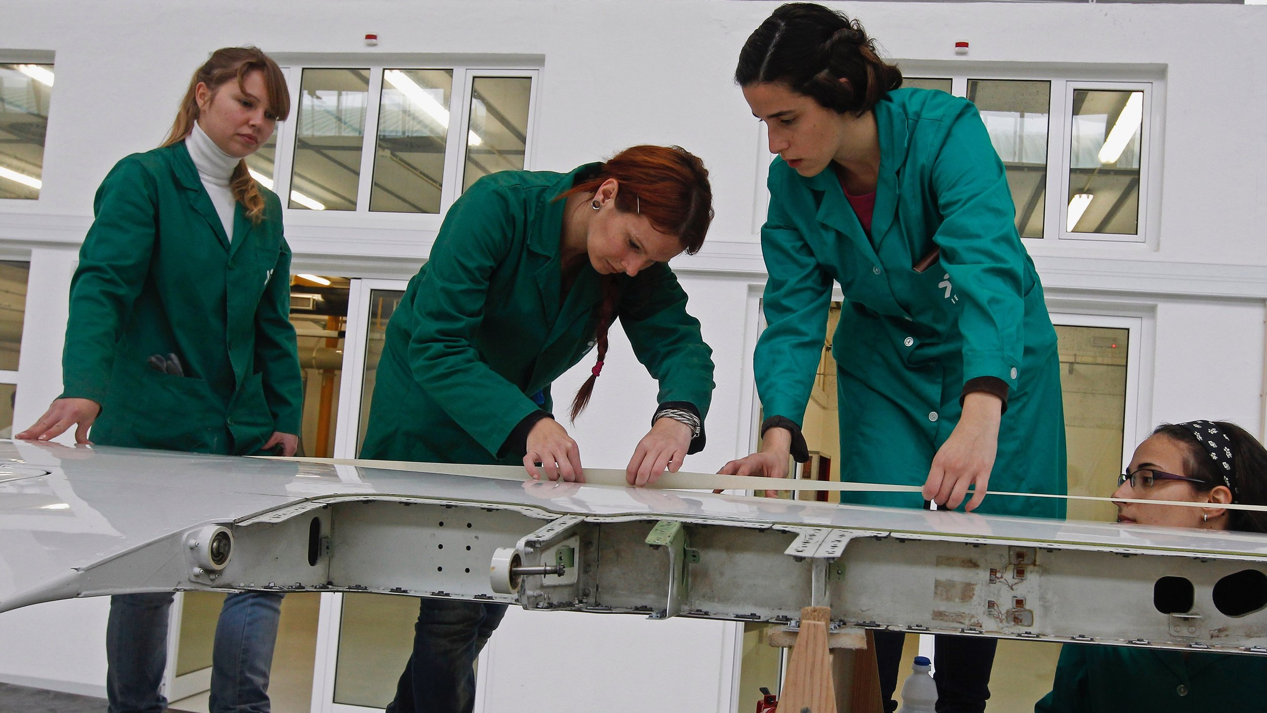 Women from the majority-female engineering class at Dartmouth work on an airplane wing. Dartmouth engineering students do not have to specialize in a particular discipline, gaining instead broad experience with many approaches to practice in the field.