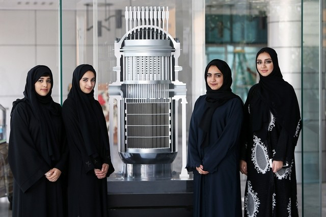 Nuclear engineers newly hired in the United Arab Emirates stand in front of a model of a nuclear reactor during orientation.