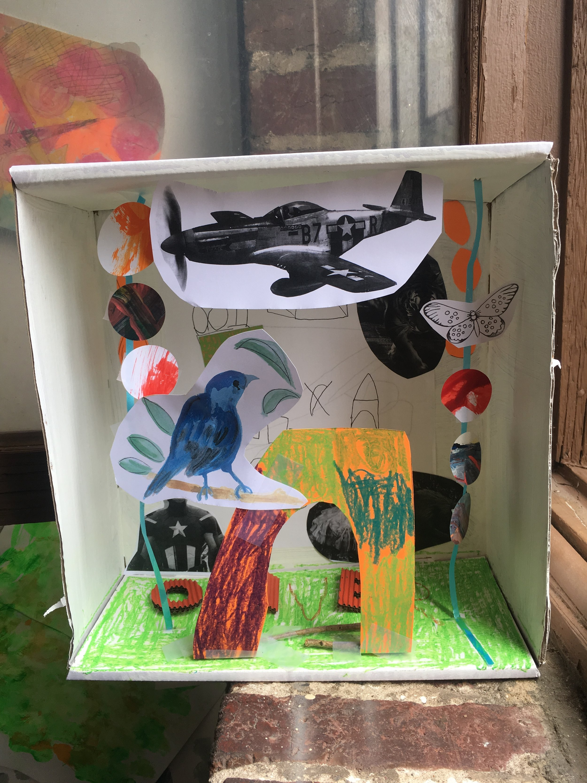 Box and Collage  - After being introduced to Joseph Cornell's shadow boxes, this little artist used his imagination to create this world in a white cardboard box, cutting and pasting provided xeroxed images, found papers and strings. Colors were added with oil crayons and colored papers.