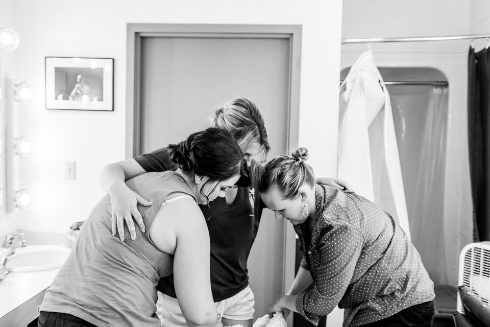 A bride leans on her friends as she puts on her wedding dress