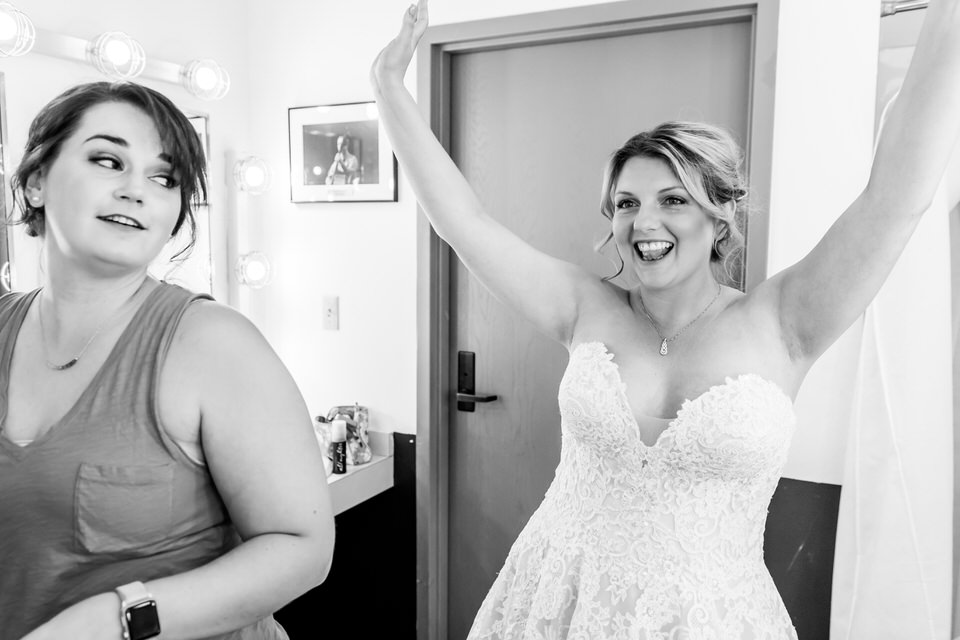 A bride raises her hands above her head as she celebrates putting on her wedding dress