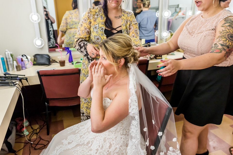 A bride puts her hands to her face after seeing herself in the mirror