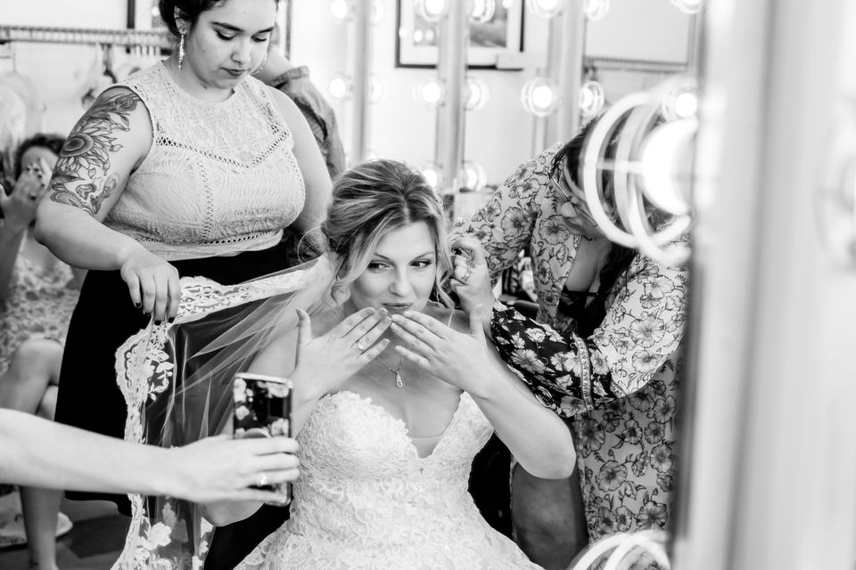 A bride blows kisses with her hands to a phone when a well wisher offers excitement over the wedding