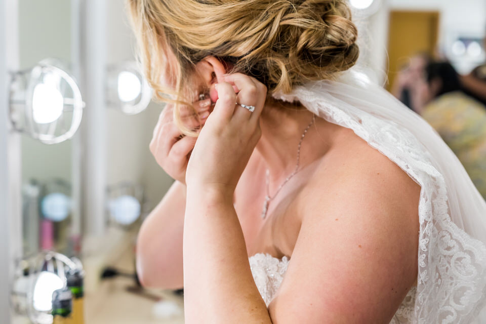 A bride puts on her earnings in a theater mirror before her wedding ceremony