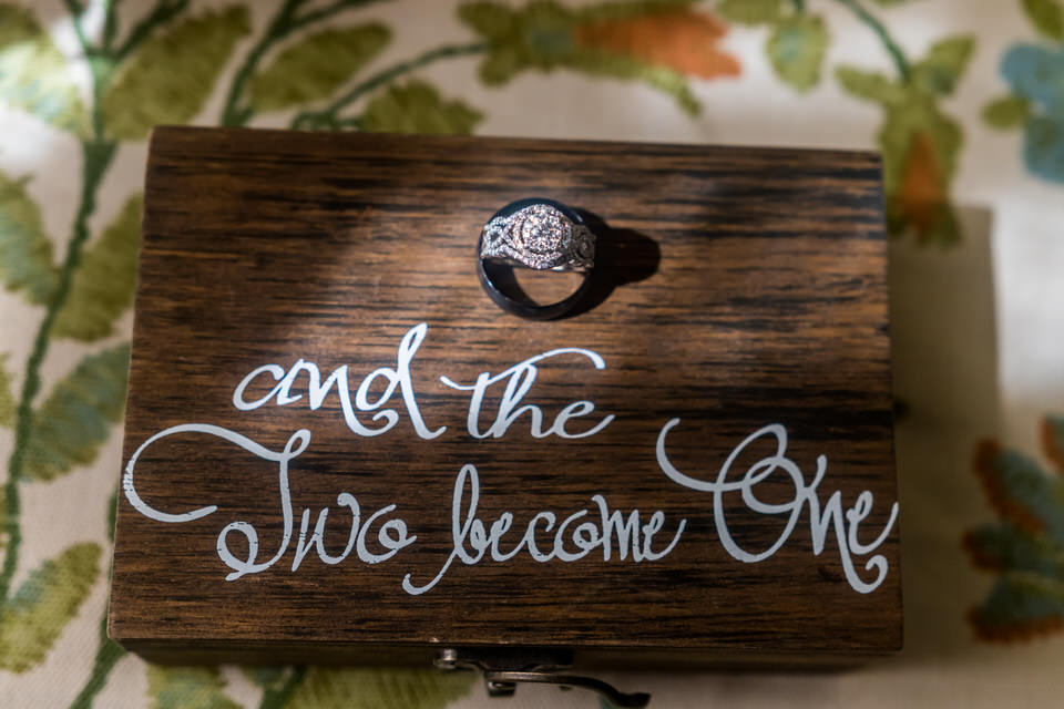 A set of wedding rings sits in a sunbeam on a box that says Mr and Mrs